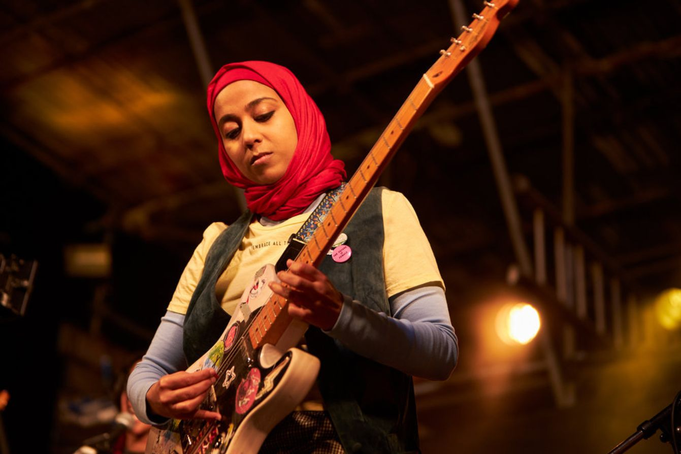 Anjana Vasan as Amina, a brown-skinned, thin woman with a hijab, who is playing the guitar in We Are Lady Parts