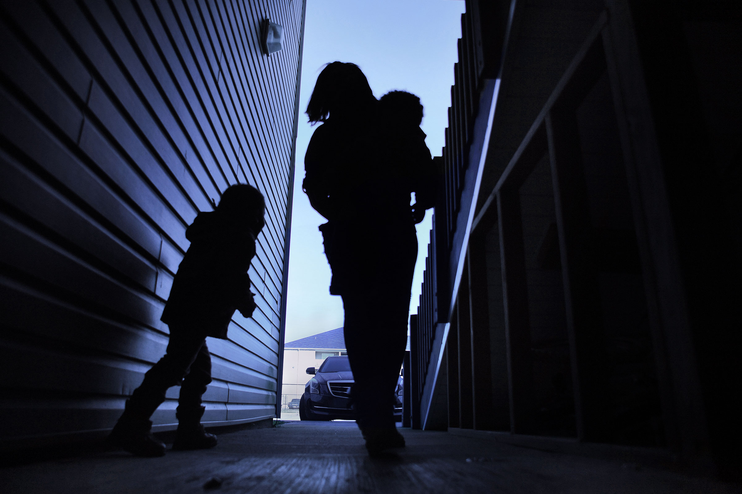 a silhouette of a mother walking with her two children, one on her hip, through an apartment complex