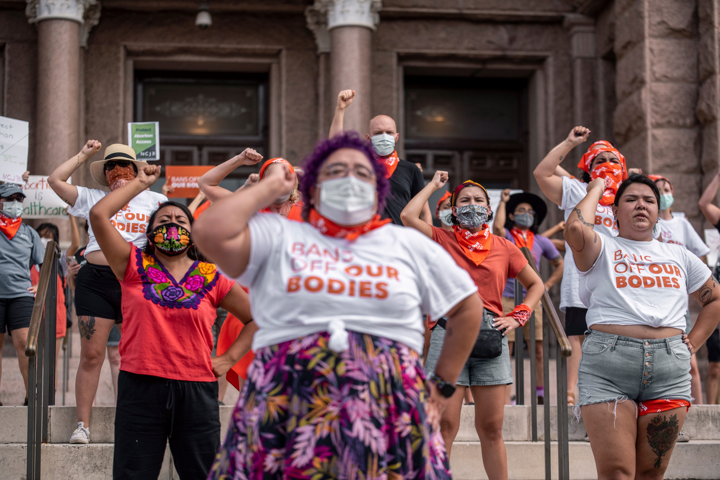 """Pro-choice protesters perform outside the Texas State Capitol on Wednesday, Sept. 1, 2021 in Austin, TX.They are wearing shirts that say """"Bans off our bodies"""" and raising their right fist"""