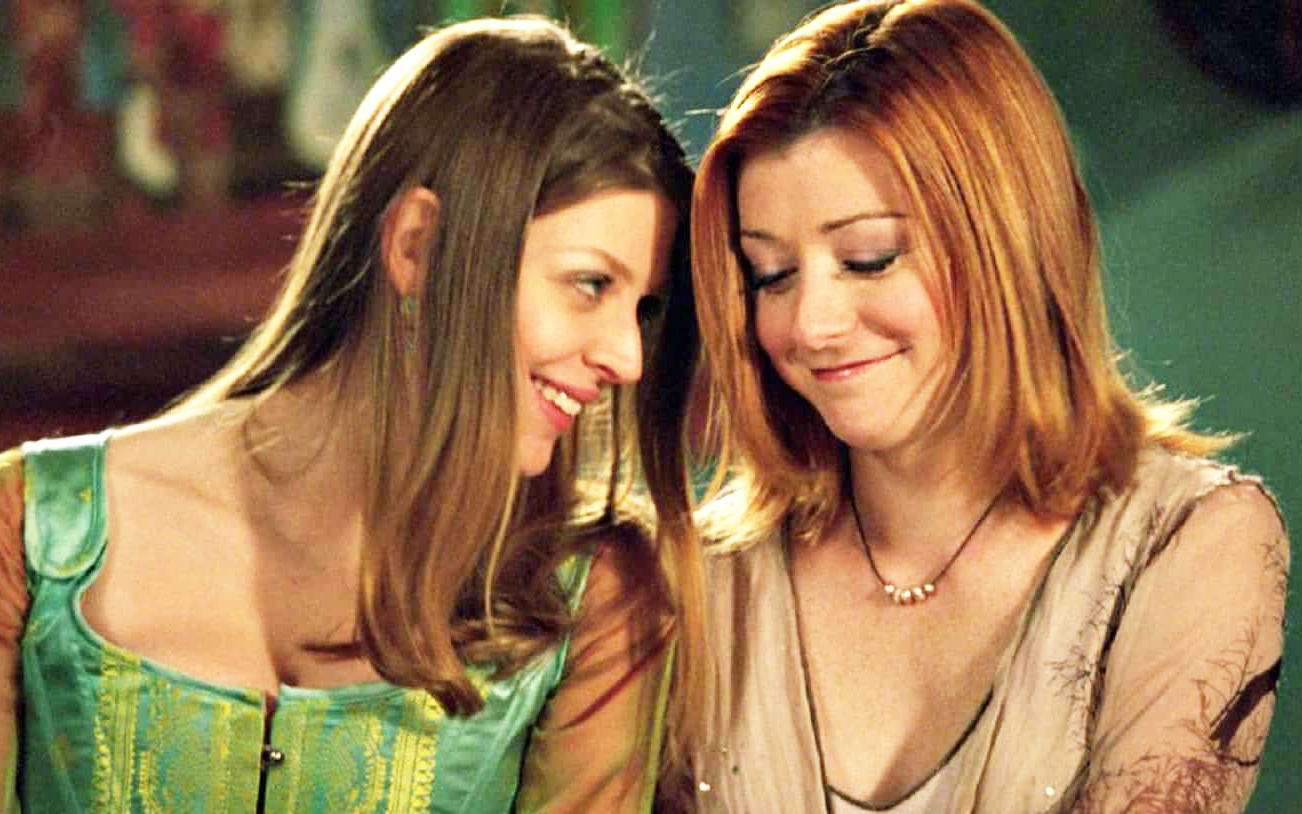 Tara (Amber Benson), left, looks lovingly at Willow (Alyson Hannigan), right, who is smiling and looking down