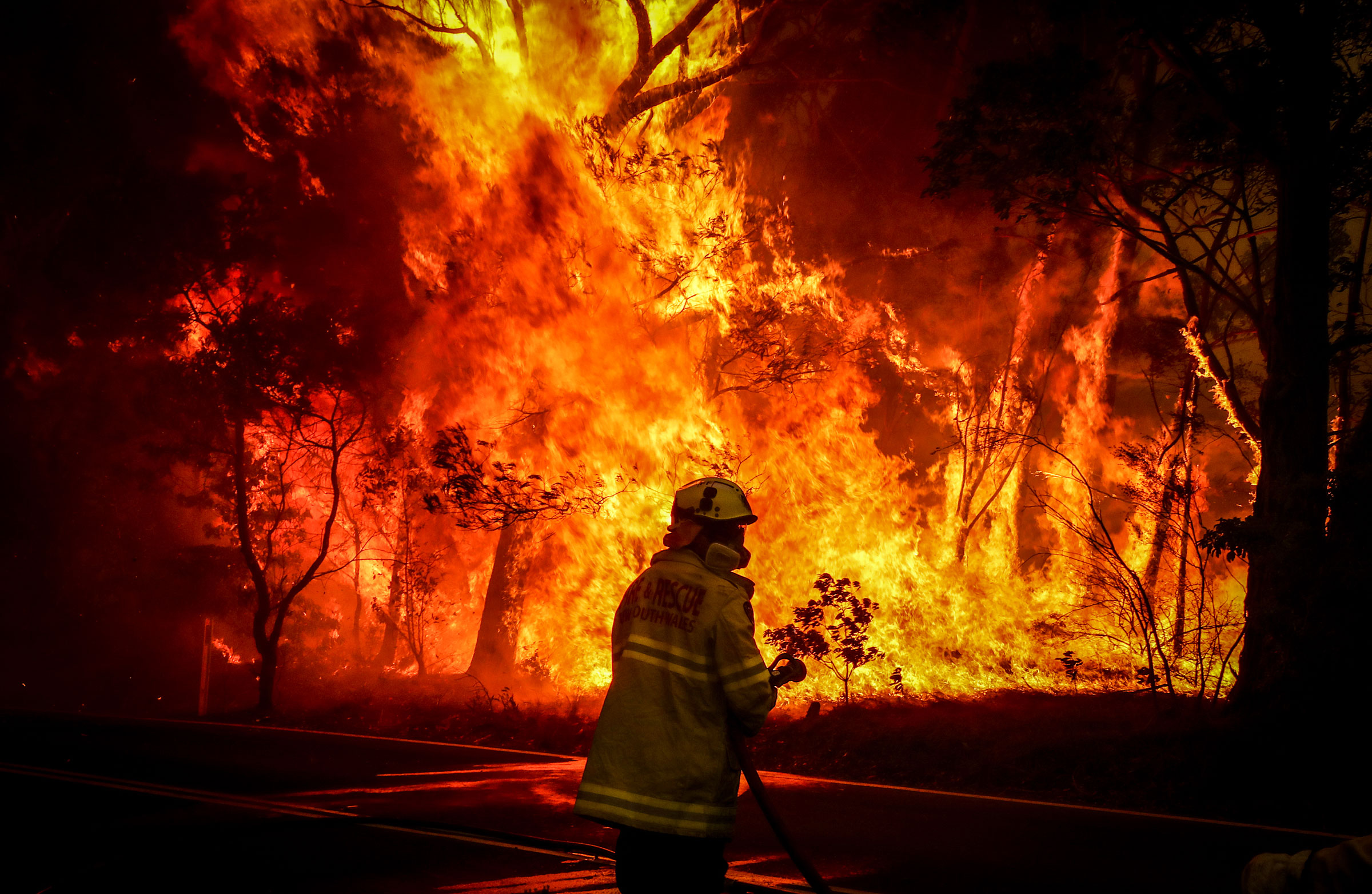 image of an Australian fire fighter in front of a huge blaze of fire