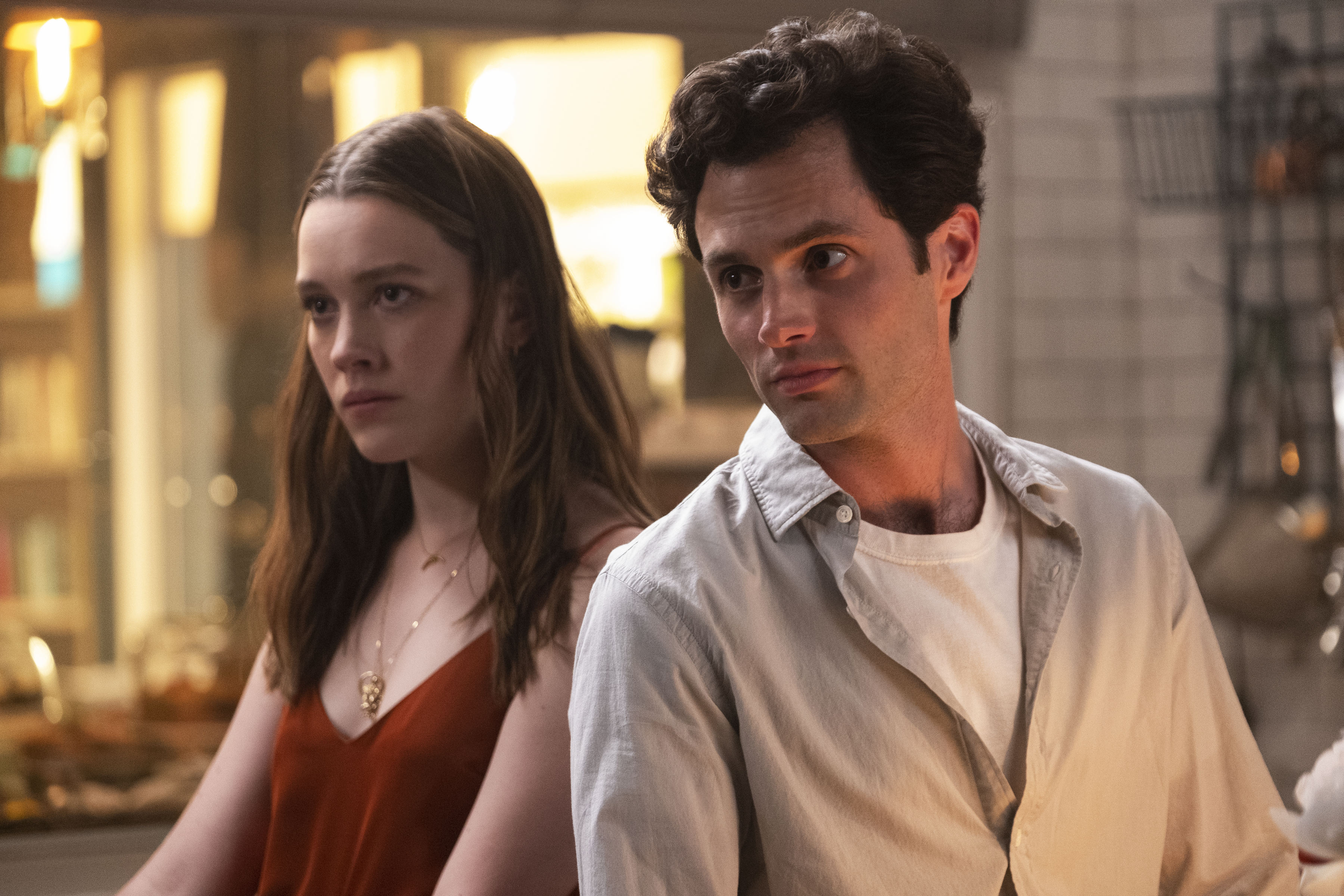 Victoria Pedretti and Penn Badgley star as Love and Joe, a white couple standing together in a kitchen, in You