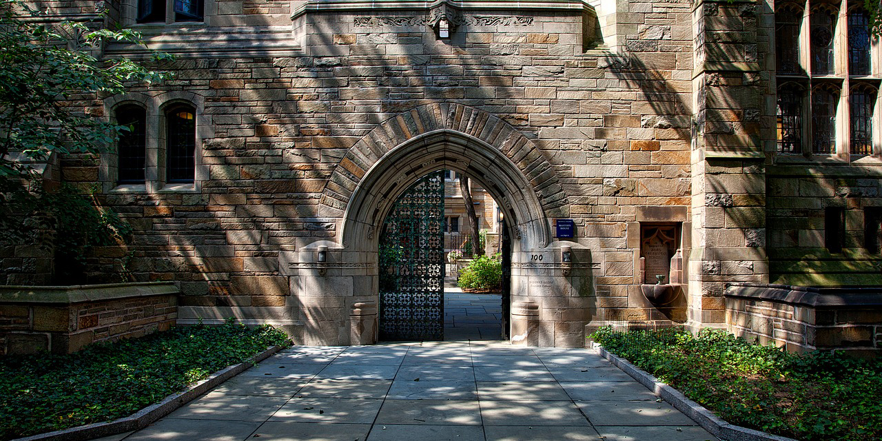 An ornate iron gate and walkway leading into a gothic style building with multicolor stones