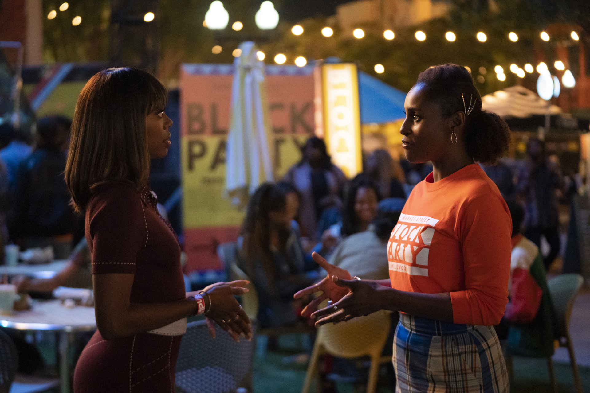 two Black women, Yvonne Orji and Issa Rae, look directly at one another during a block party on Insecure