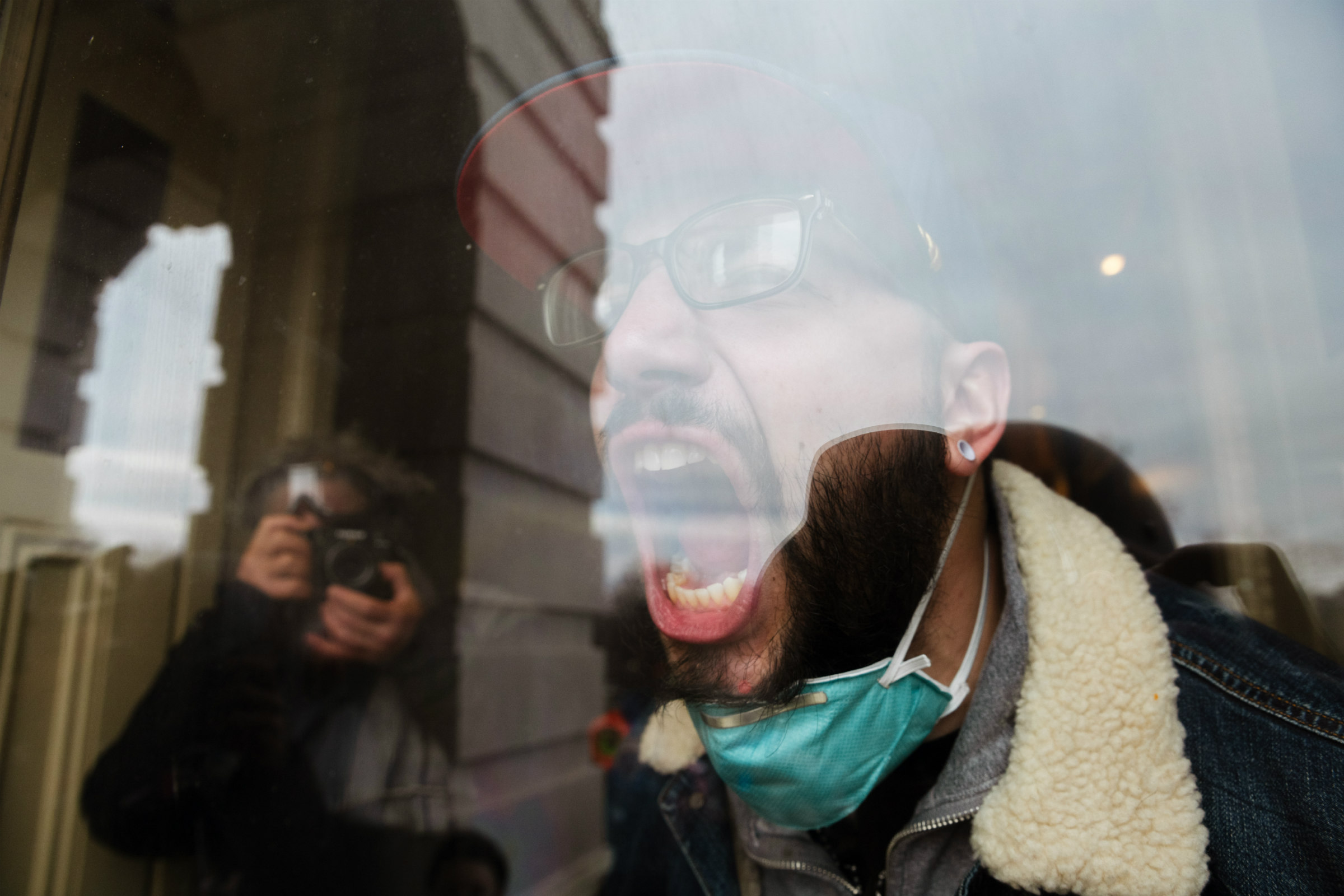 a white person wearing a blue hat scream and a mask around his chin screams from a behind a glass at a camera