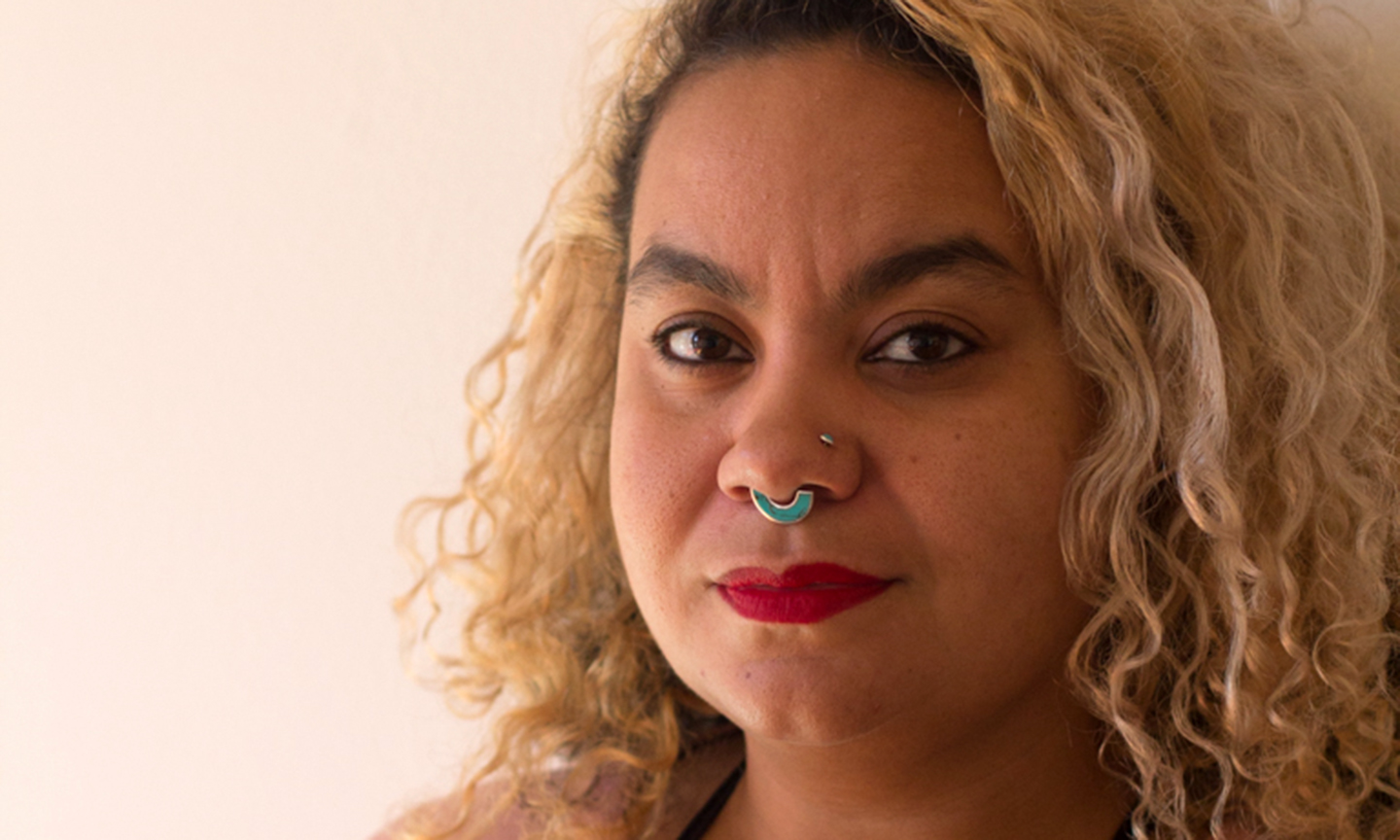 a photo of adrienne maree brown, a lightskinned Black person with a bull nose ring and shoulder-length blond, curly hair