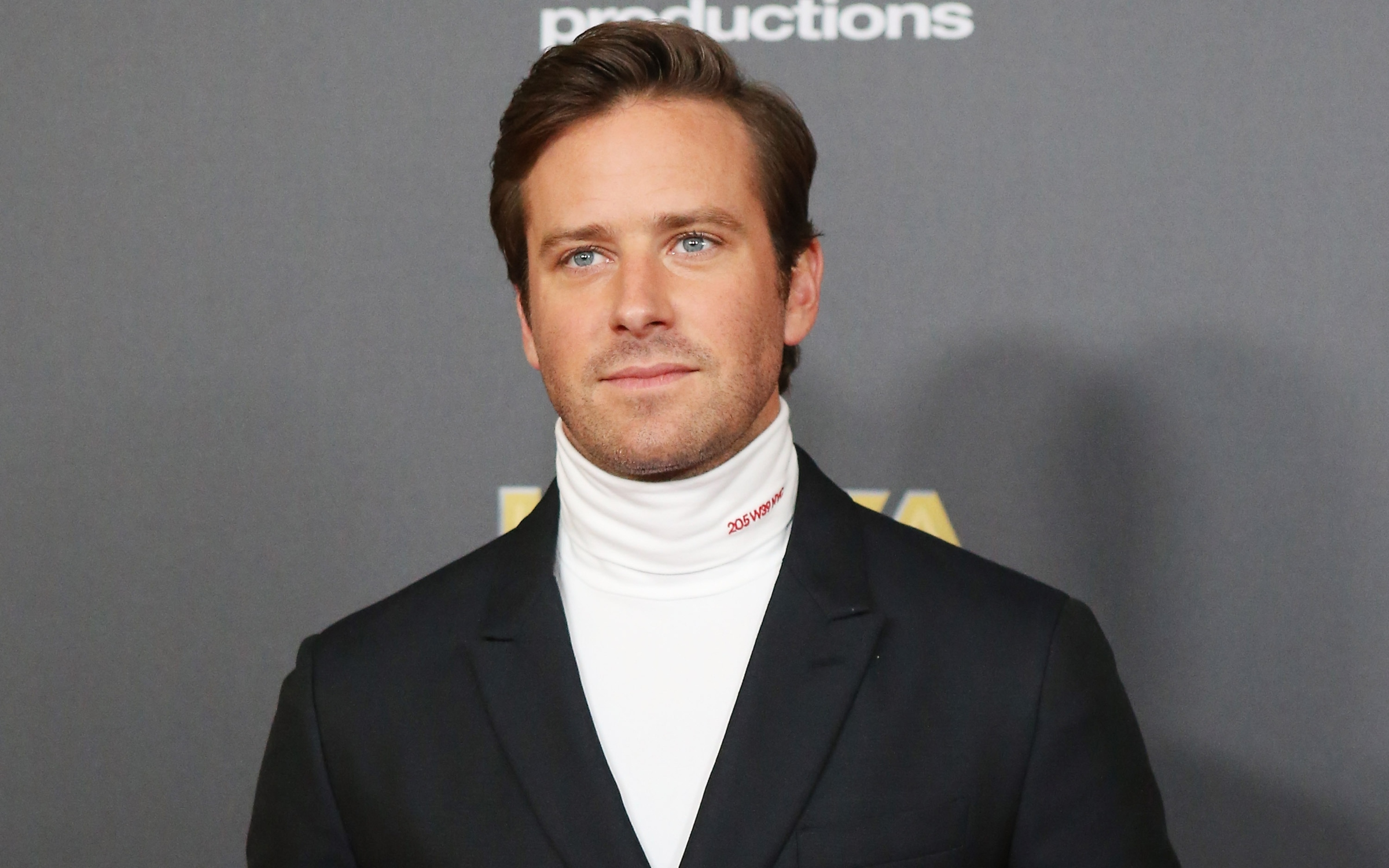 Armie Hammer, a white man with light brown hair and blue eyes, wears a white turtleneck under a black blazer.