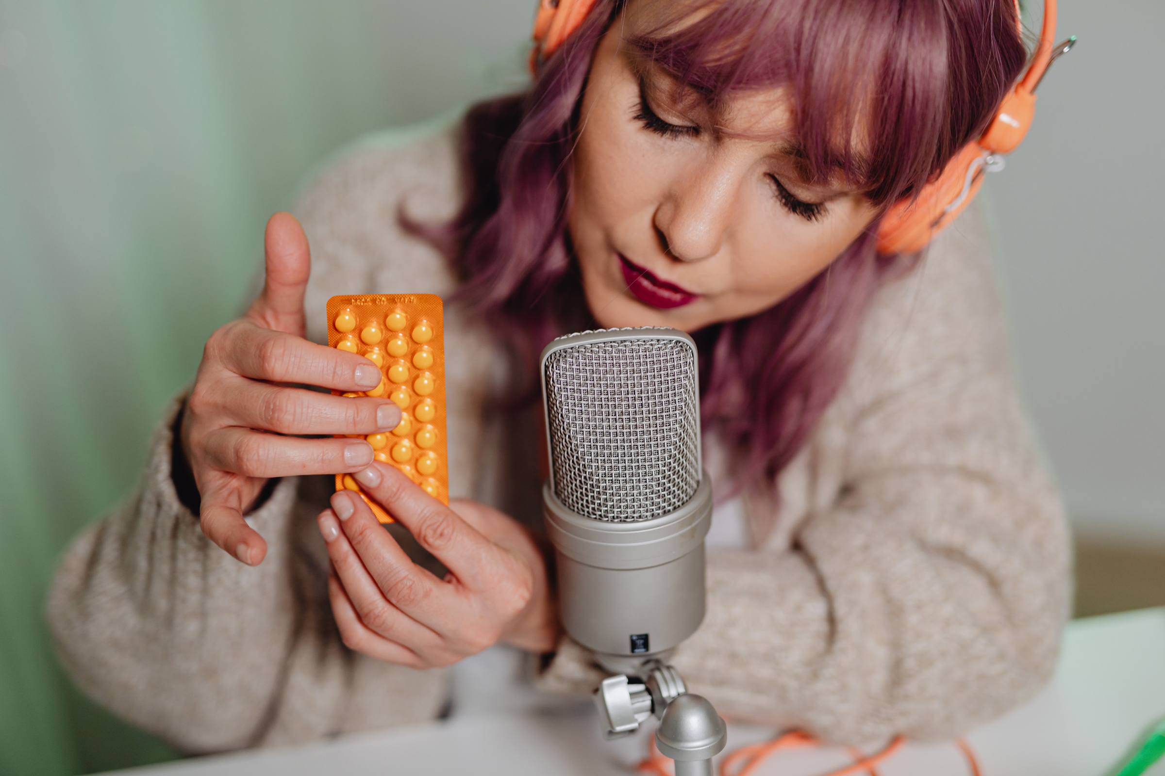 A white woman with purple hair holds an orange wrapper with bumps on it in front of a microphone to make ASMR sounds.
