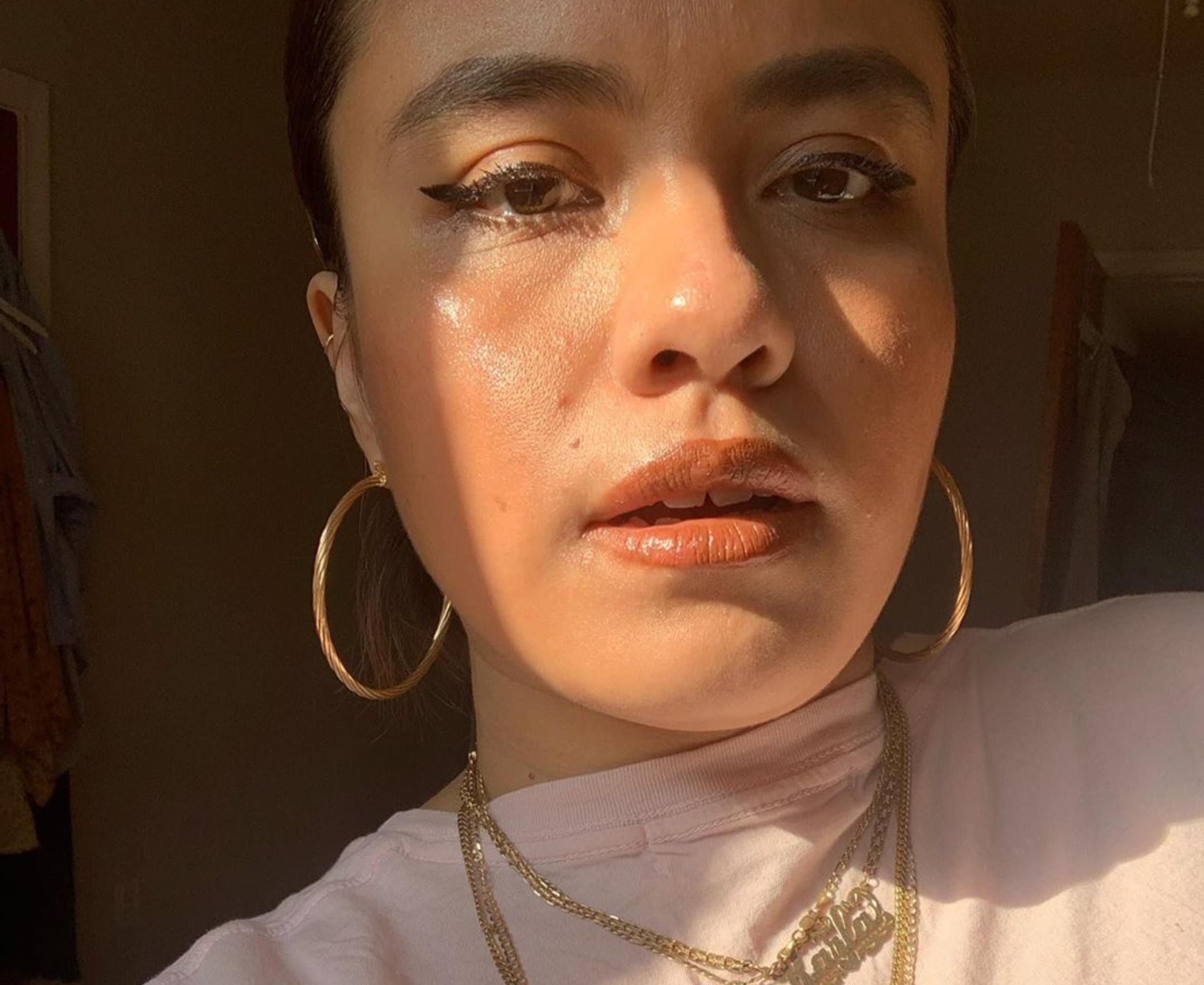 Author Karla Cornejo Villavicencio, who wears gold jewelry and takes a selfie.
