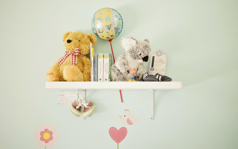 a photo of a nursery shelf with a stuffed koala bear, a stuffed teddy bear, and other gifts for a baby