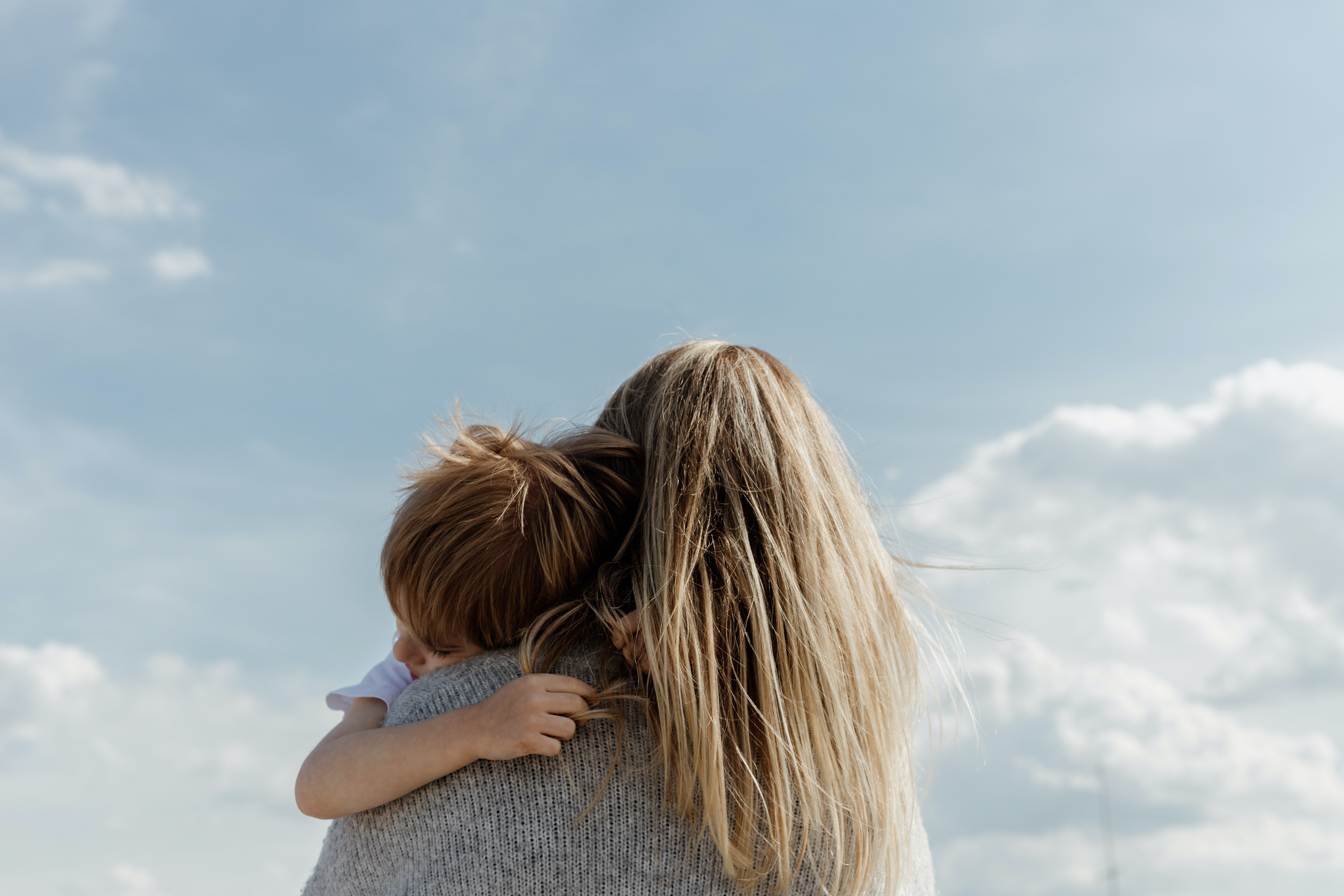 A mom holds her child, both of their faces obscured. The sky is bright blue behind them.