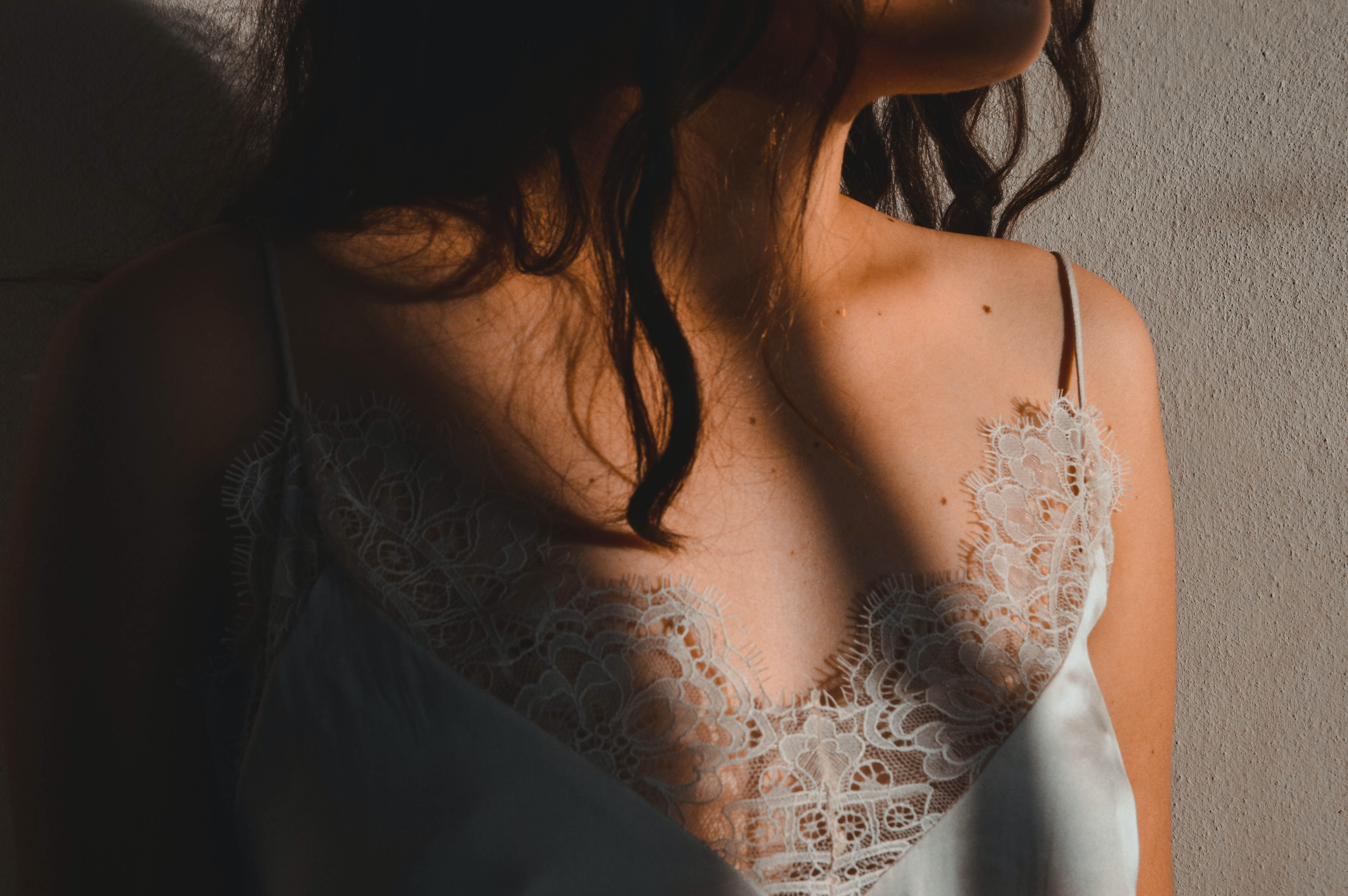 A close-up of a woman in a lace top, her face obscured.