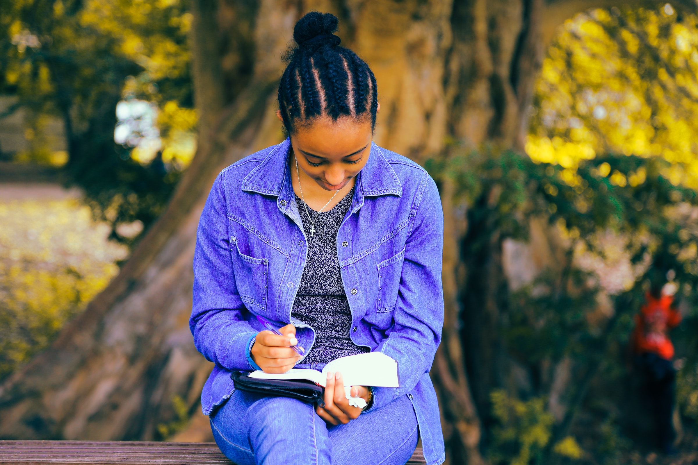 A young Black woman with braids sits on an outdoor bench reading a book on her lap. She's wearing a denim jacket and jeans and there is a big tree with yellow flowers behind her.