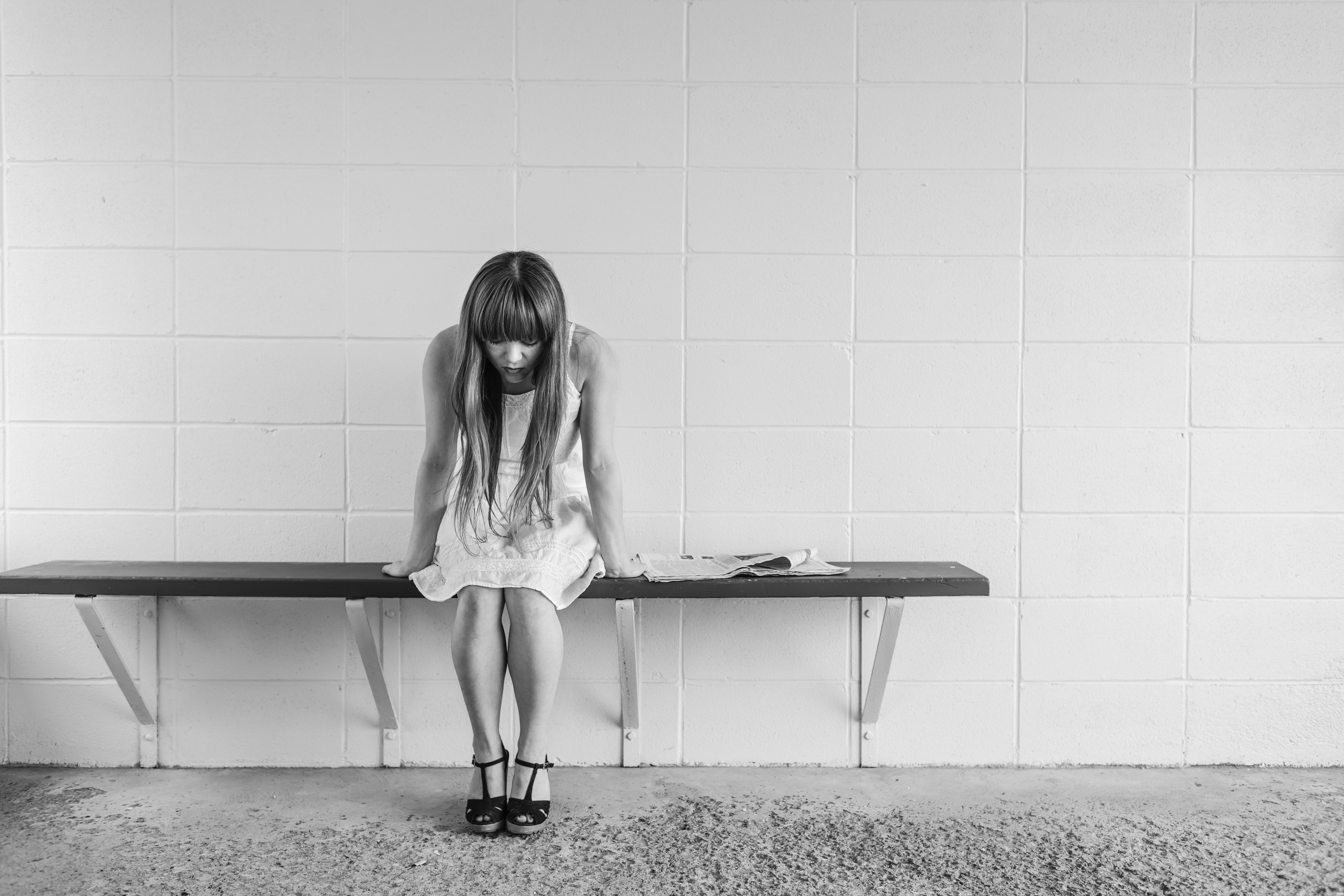 black and white image of a depressed person sitting on a bench