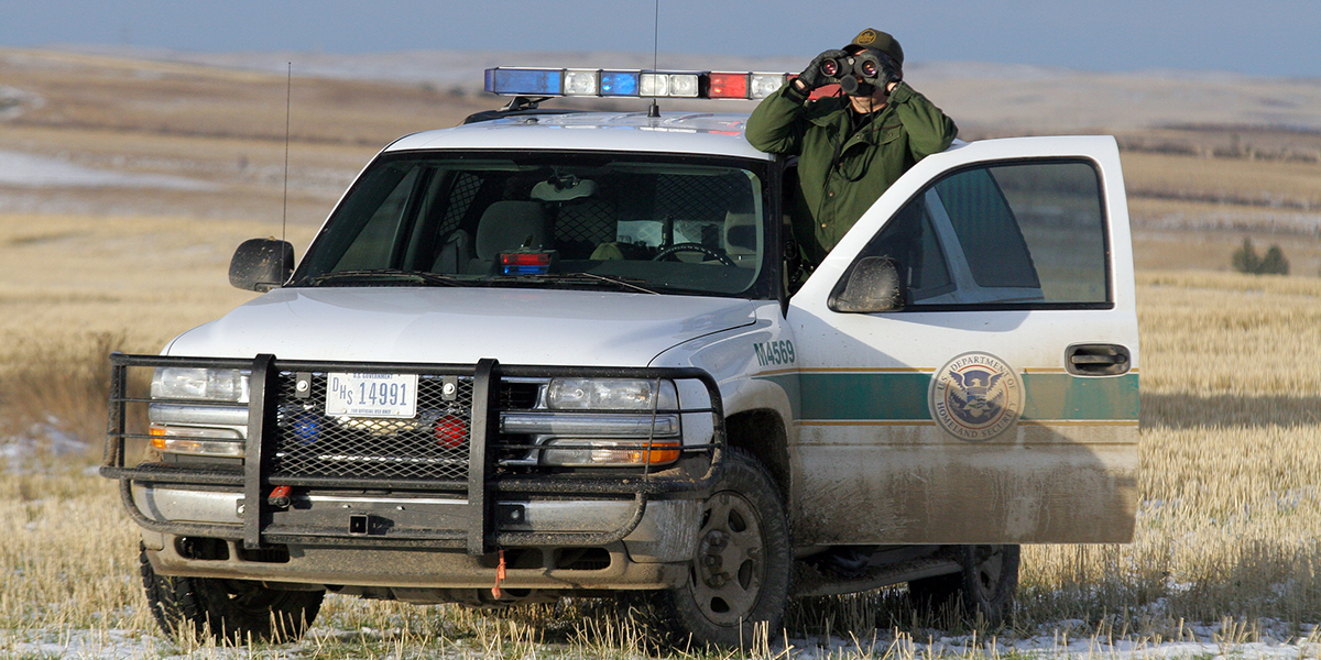 A border patrol agent looks through binoculars while standing next to muddy U.S. Department of Homeland Security vehicle