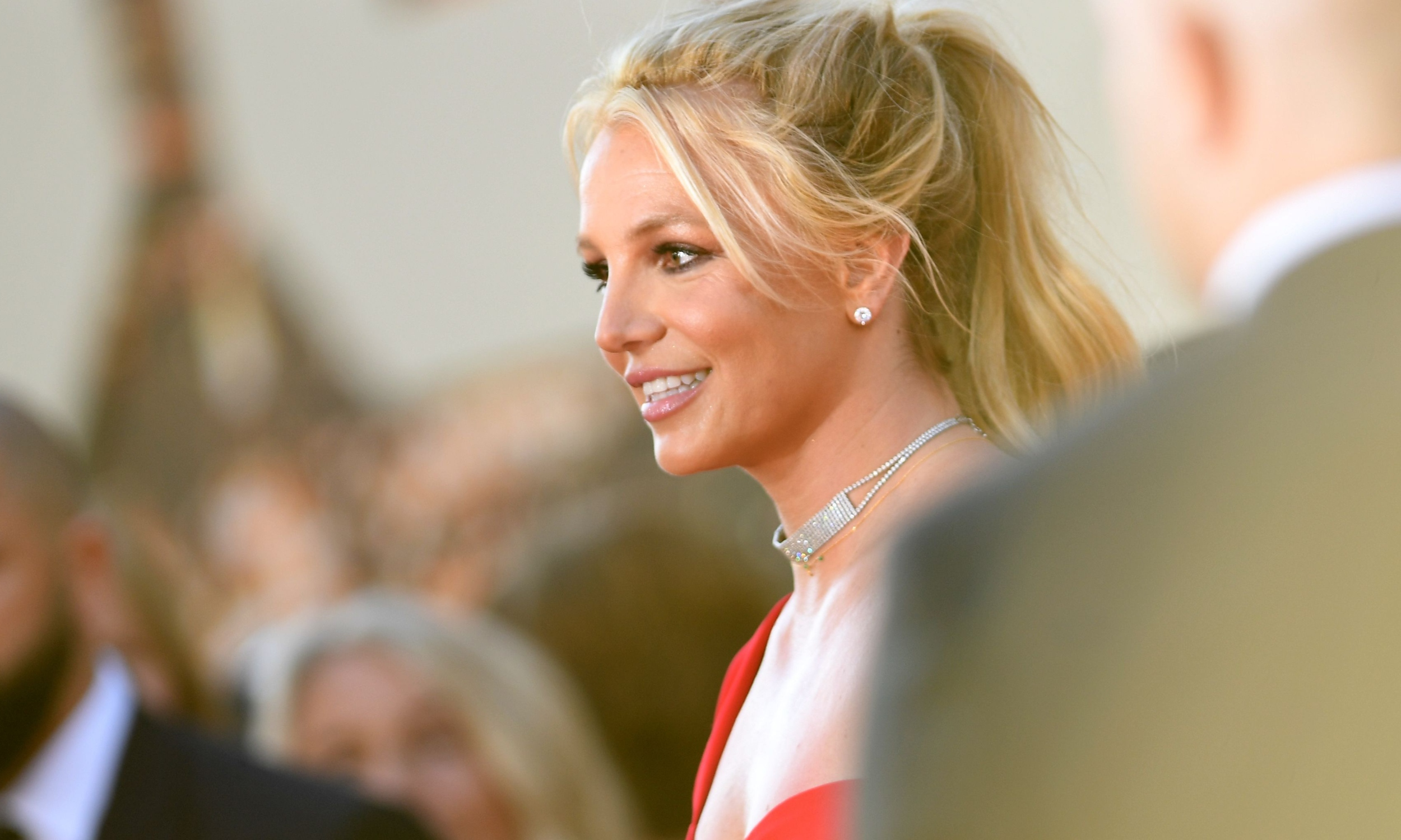 Britney Spears wears a red dress. Her hair is blond and in a high ponytail.