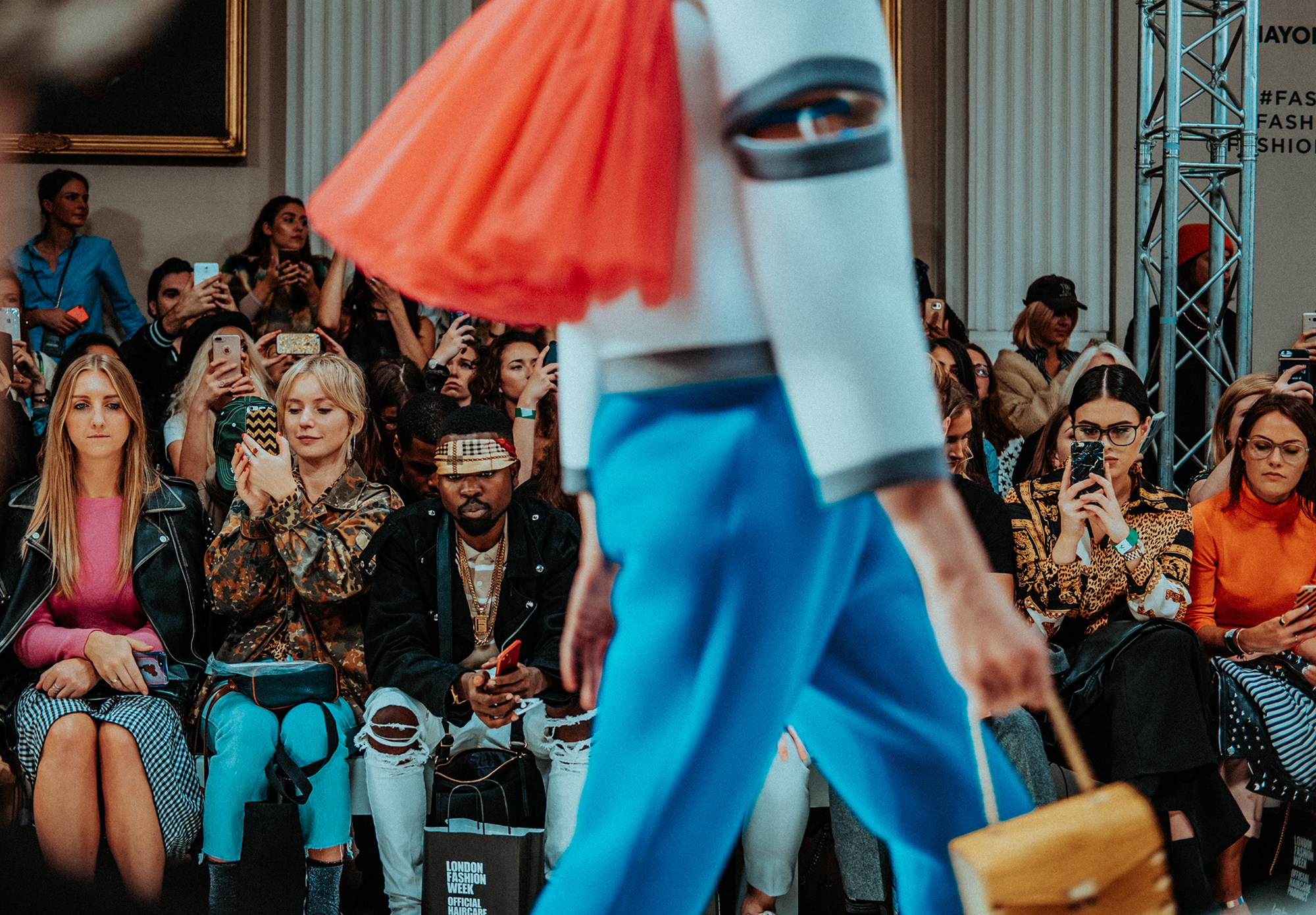 Image of people sitting front row at a fashion show while a model walks by