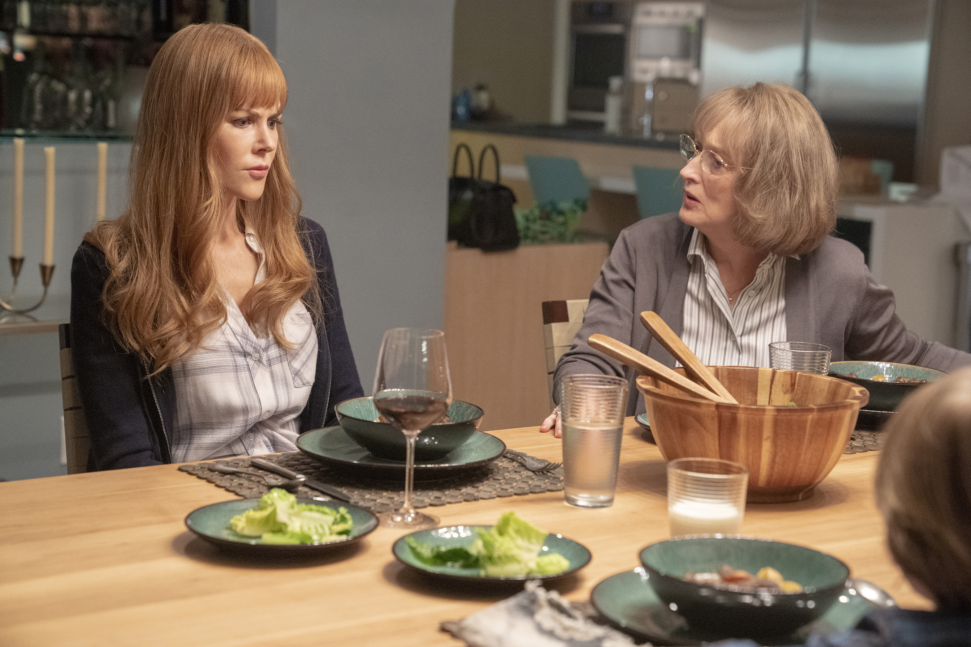 Nicole Kidman, a redheaded white woman, sits beside Meryl Streep, an older white woman with gray hair and glasses, on Big Little Lies