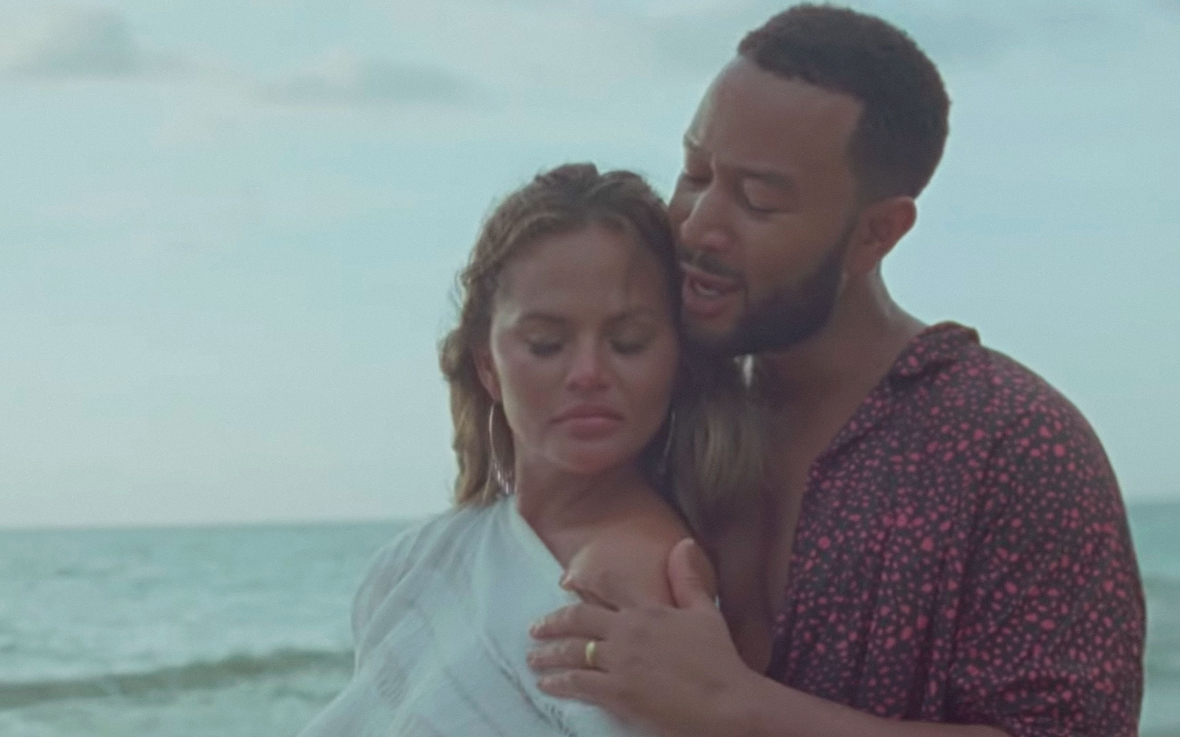 Chrissy Teigen leans against husband John Legend on a beach.