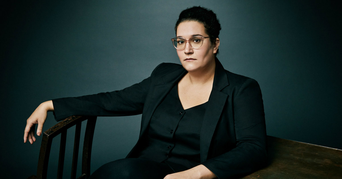 A woman in large glasses, Carmen Maria Machado, sits against a table while looking into the camera.