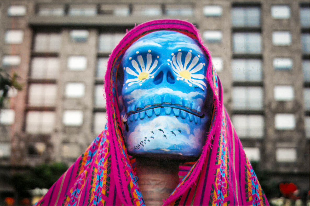 closeup of a painted Dia de Los Muertos blue mask draped in an embroidered magenta textile