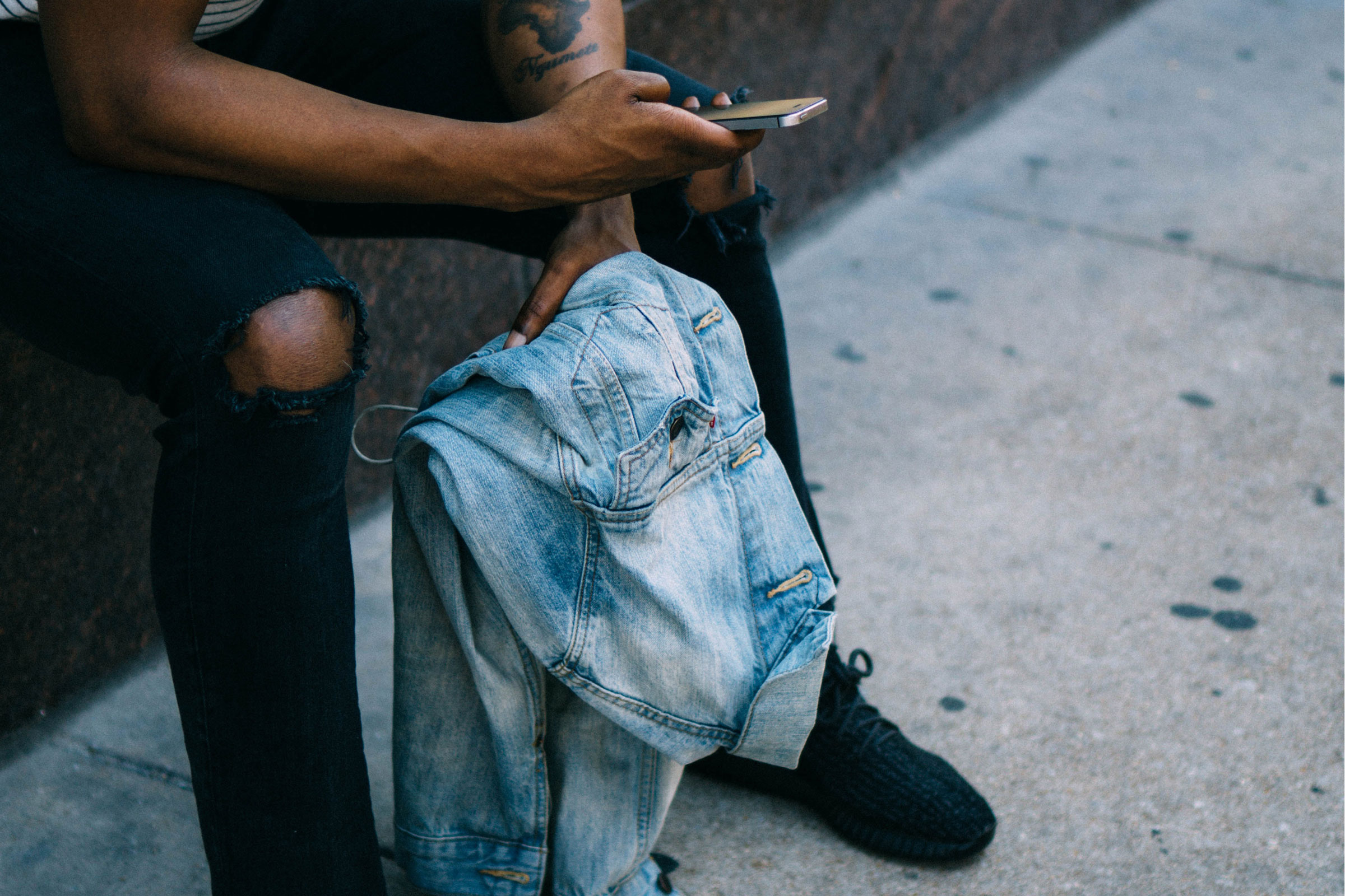 A Black person's hand scrolls through their iPhone.