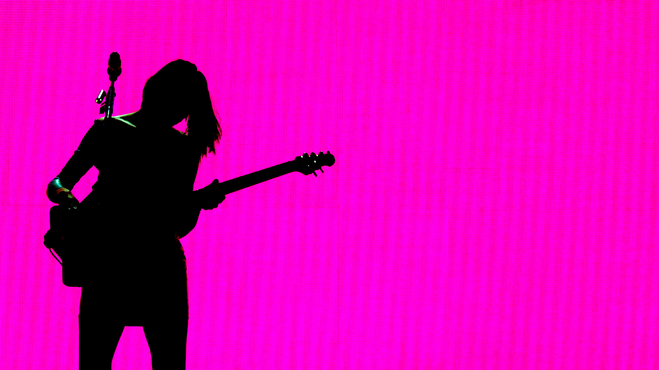 St. Vincent plays her guitar in front of a neon pink background.