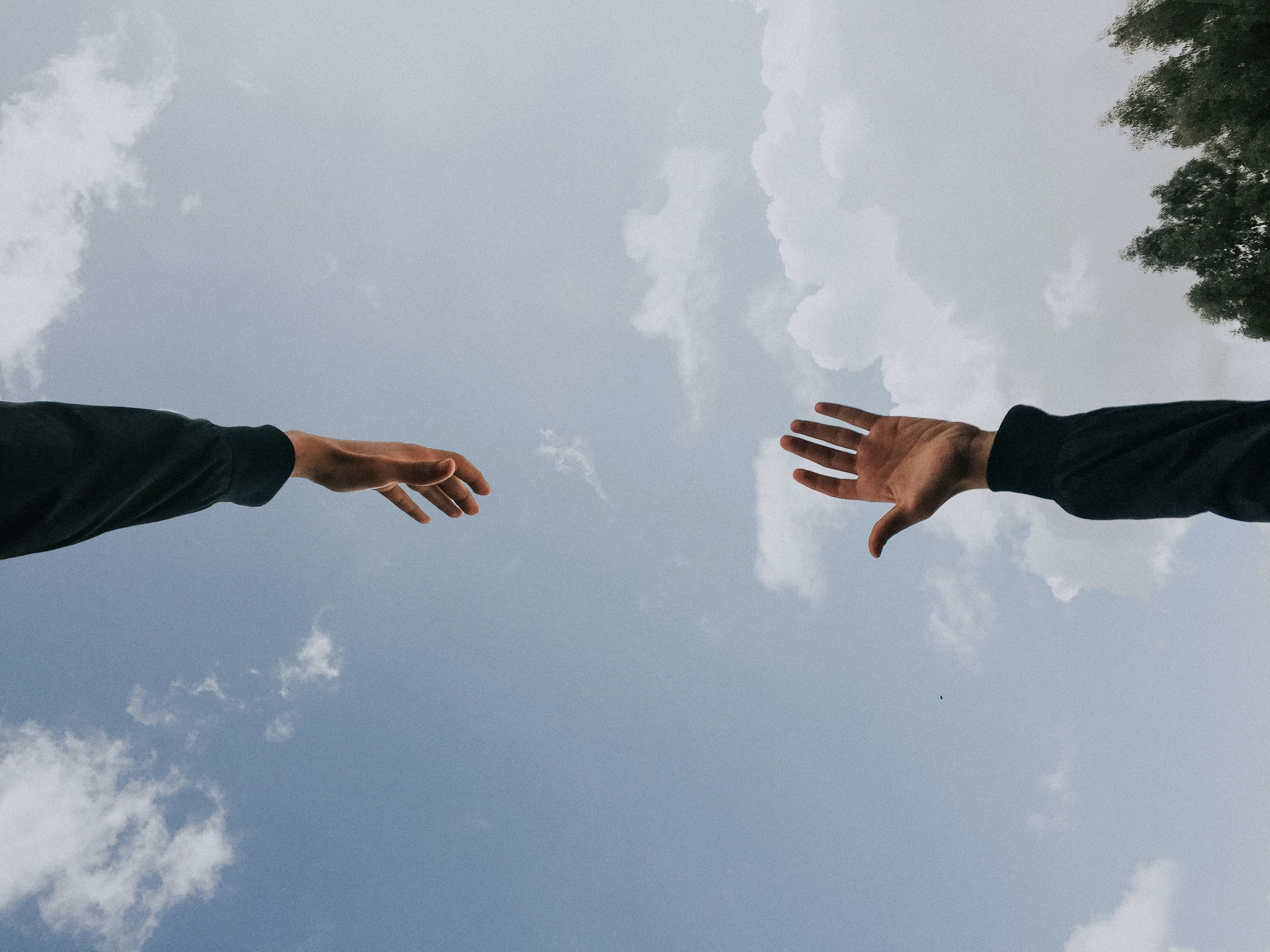 Two hands reaching for each other with a sky in the background.