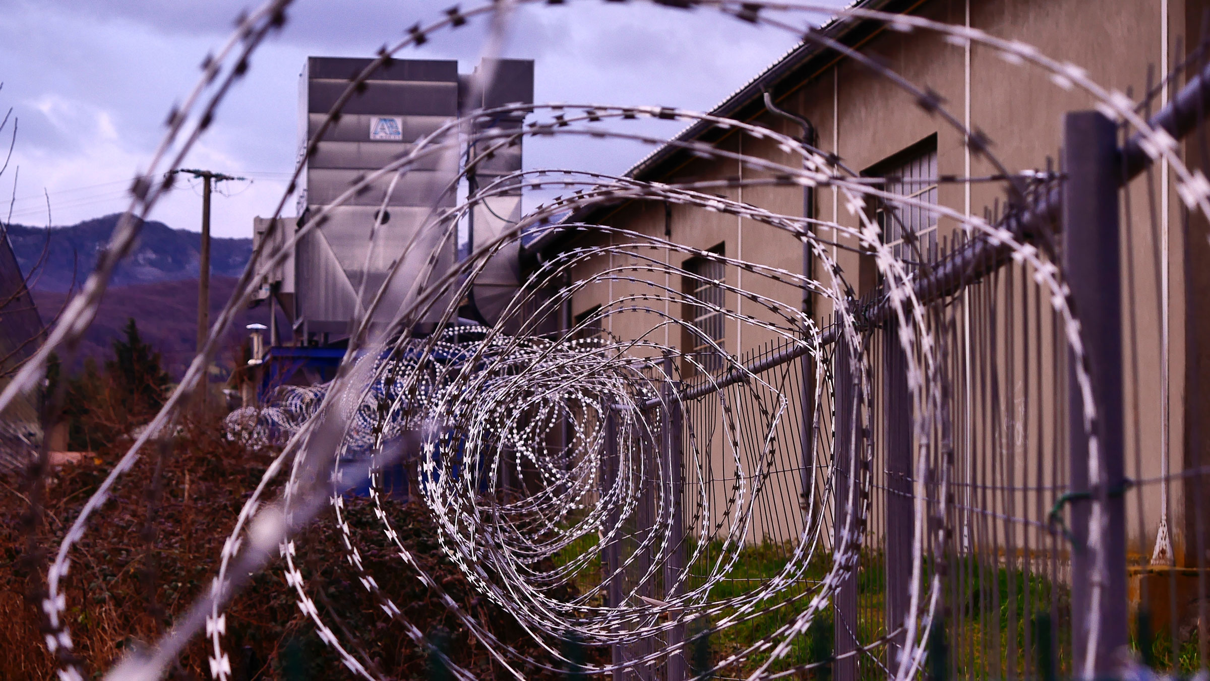 Barbed wire separates a prison wall from nature