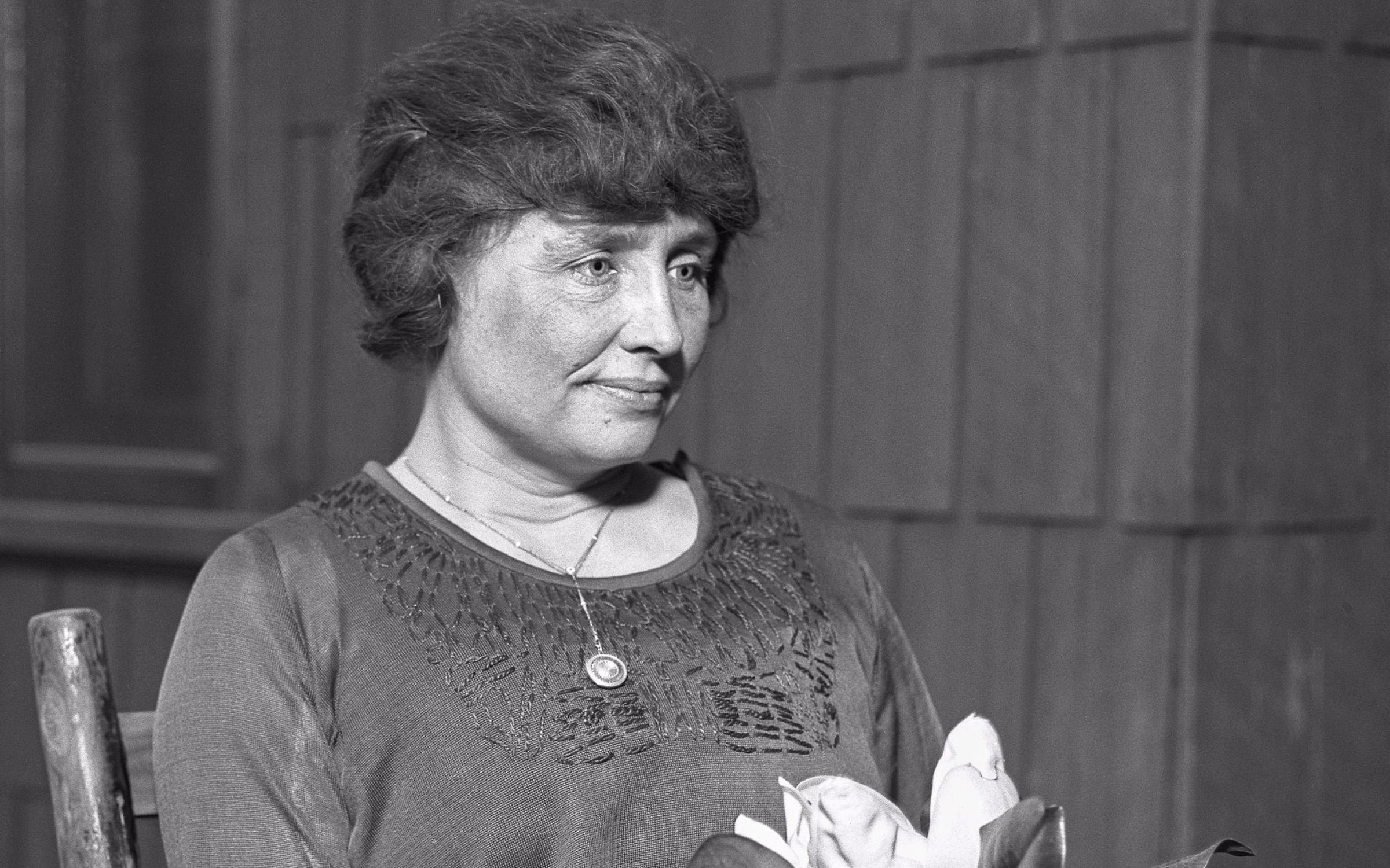 Helen Keller, a white woman, sits while holding a flower. Her hair is dark and sits on her head in a bun. The photo is in black and white.