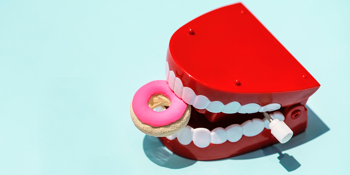 A plastic donut inside a windup chattering teeth toy against an aqua background