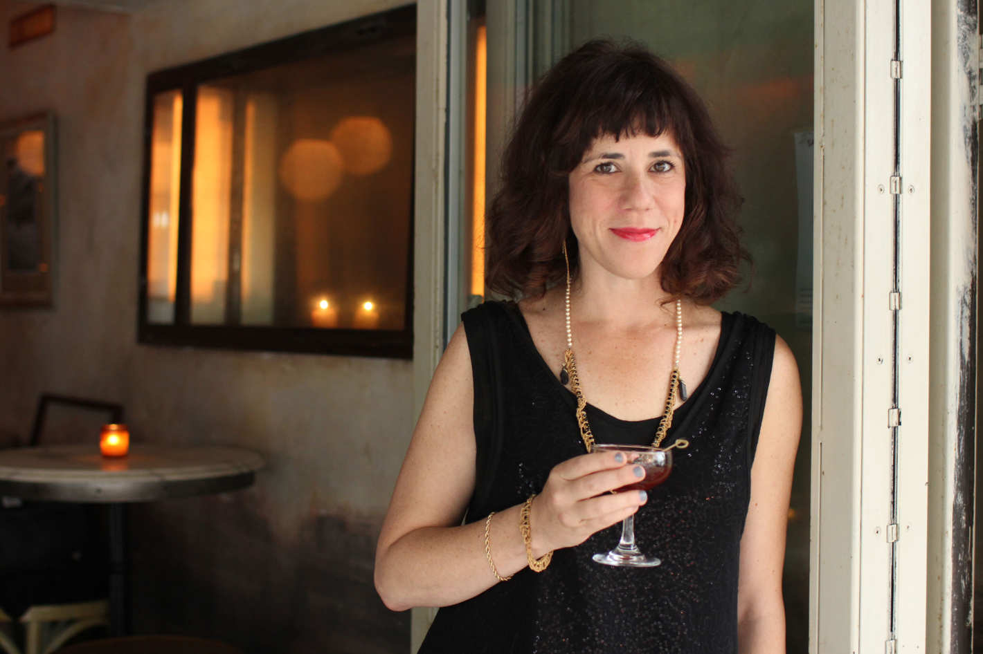 Jami Attenberg, a white woman with shaggy brown hair is leaning against a door frame holding a drink in one hand, while she softly smiles