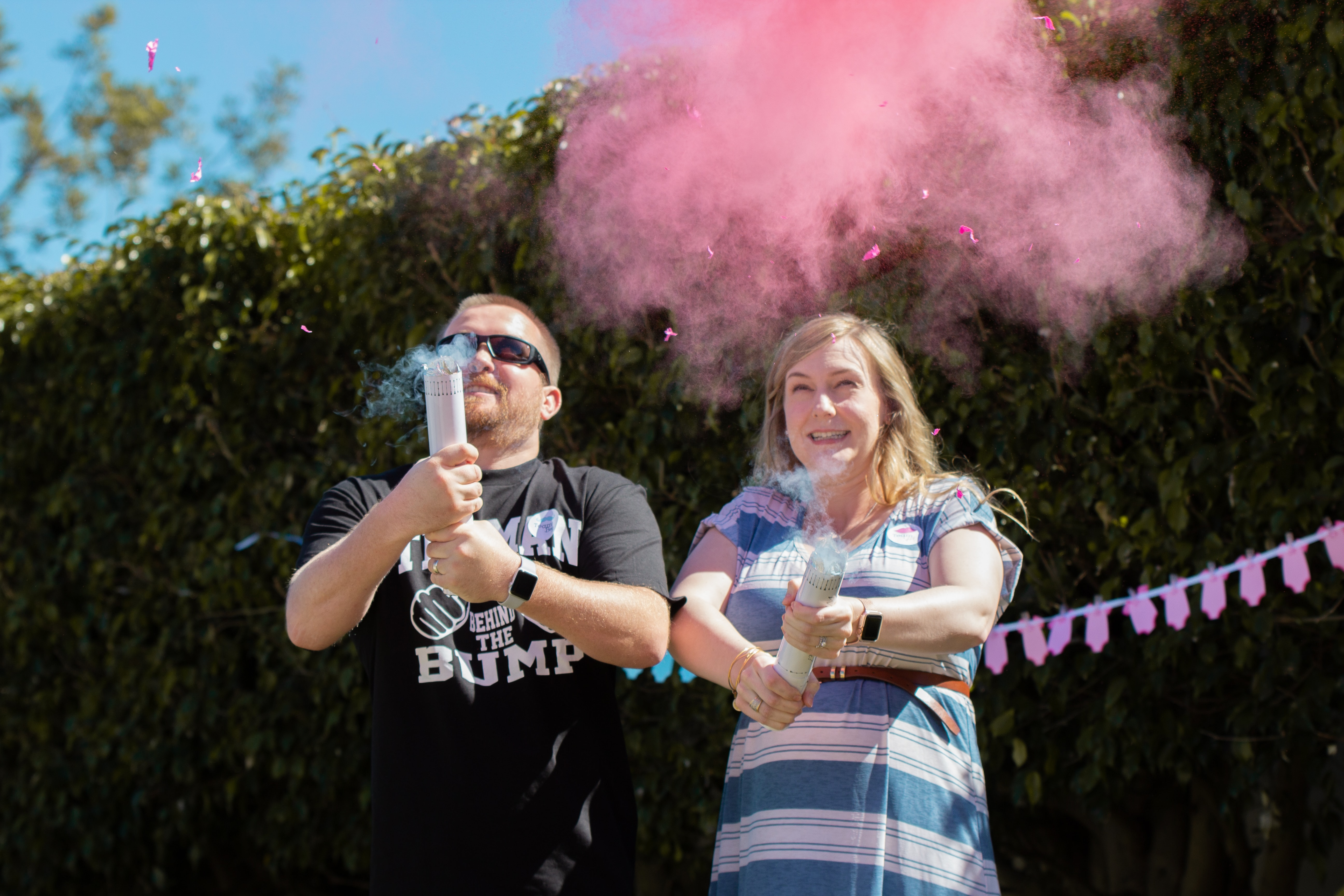 A gender reveal party: a white couple holds a device that releases blue or pink smoke.
