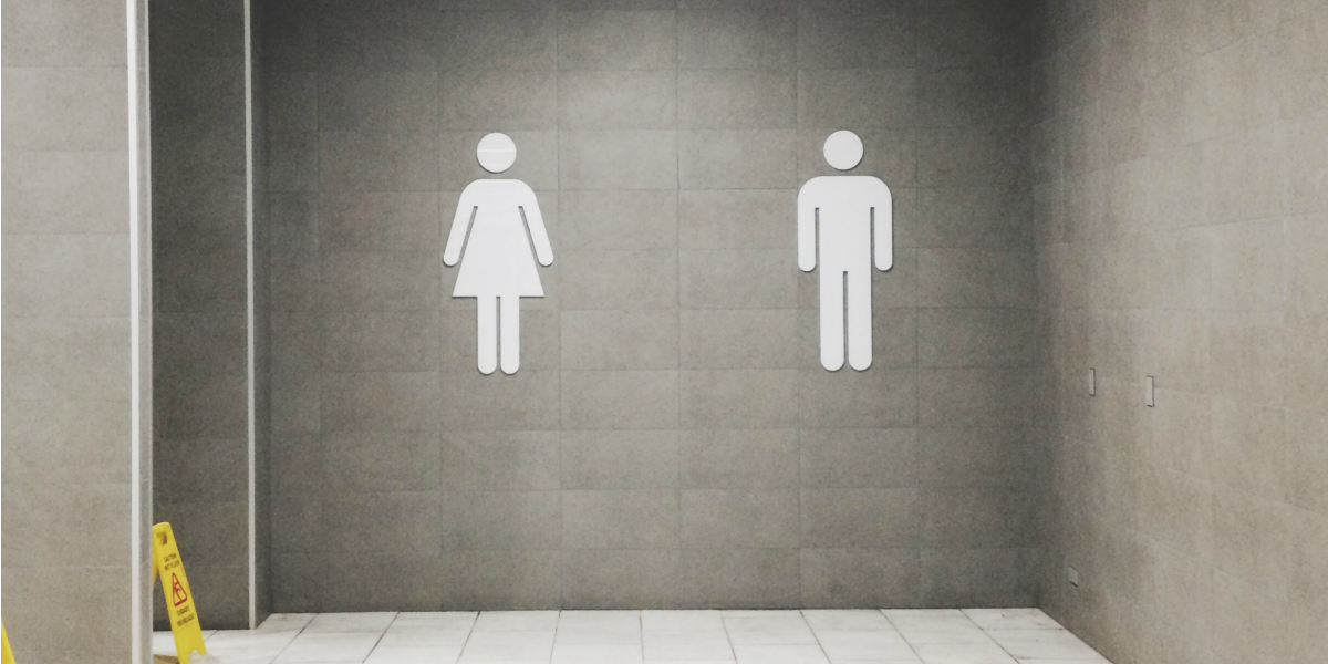 A grey bathroom wall sign designating the men's restroom and women's restroom