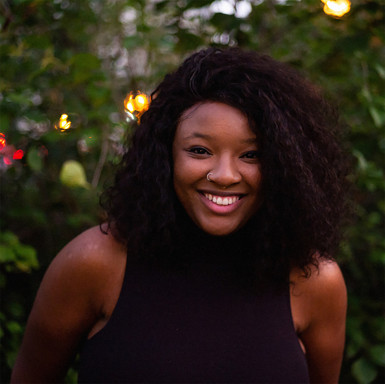 Leah Johnson, author of You Should See Me in a Crown. Leah is a Black woman with curly hair and a nosering. She wears a black mockneck tank top and smiles at the camera.