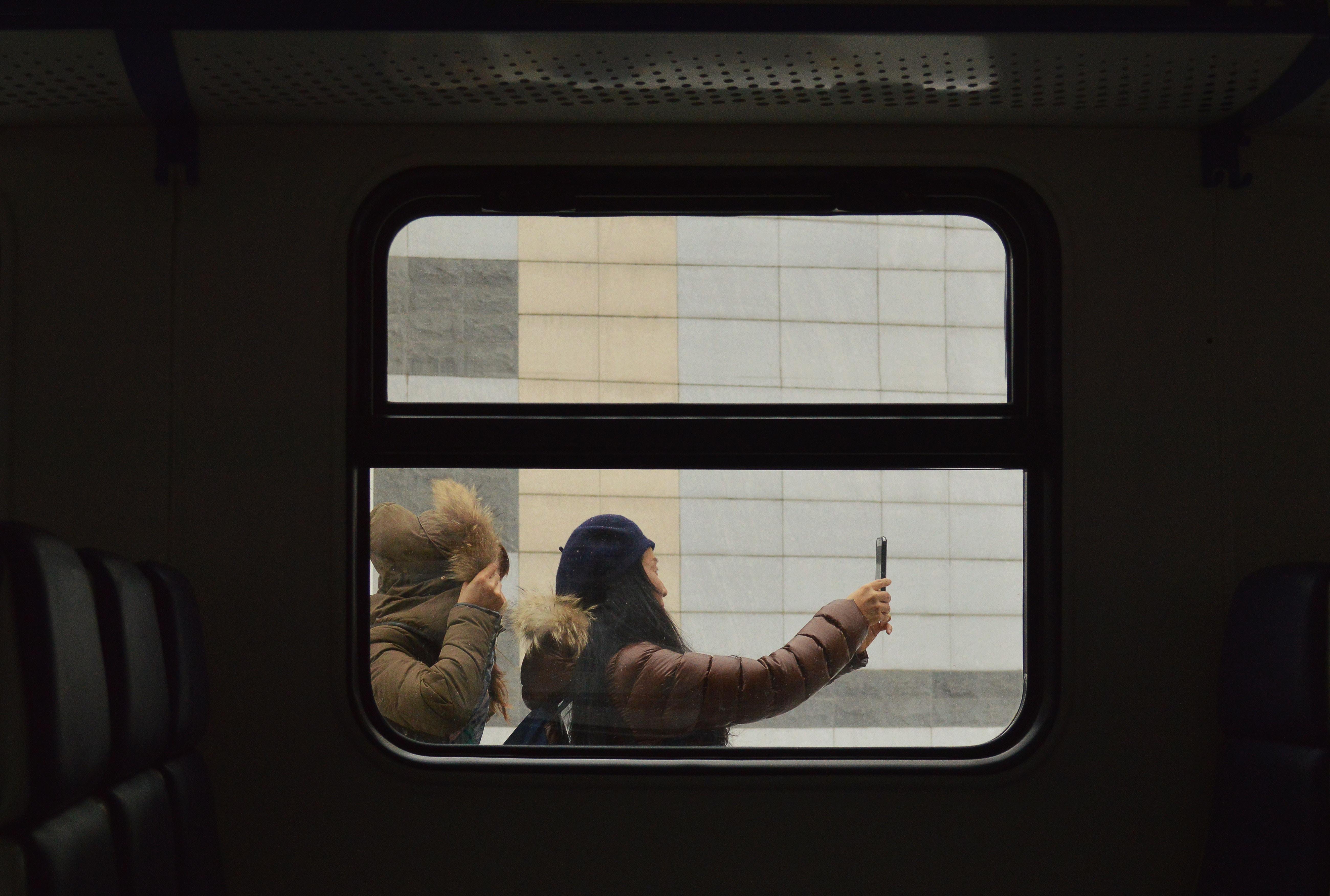 woman on train platform taking selfie