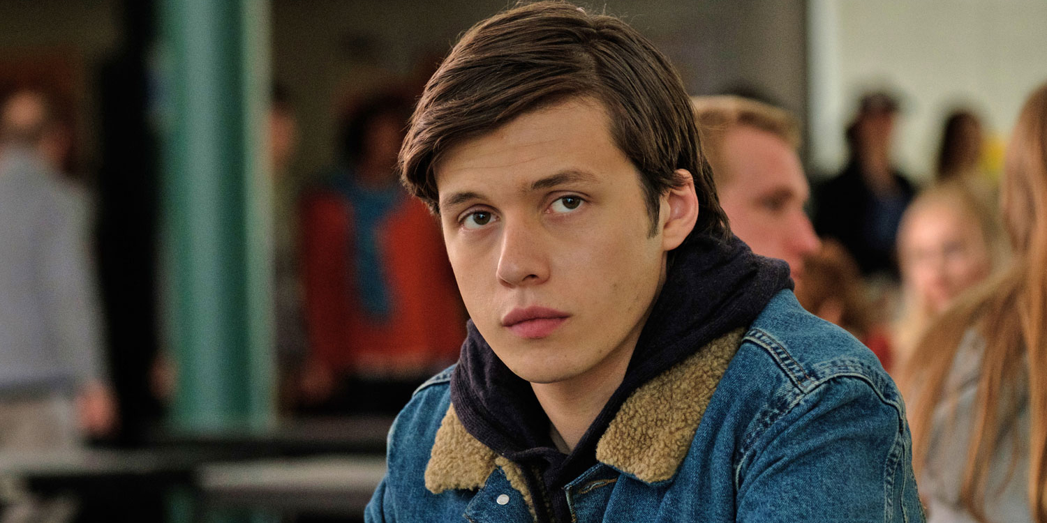 Nick Robinson with a serious look on his face, wearing a jean jacket in what looks like a cafeteria