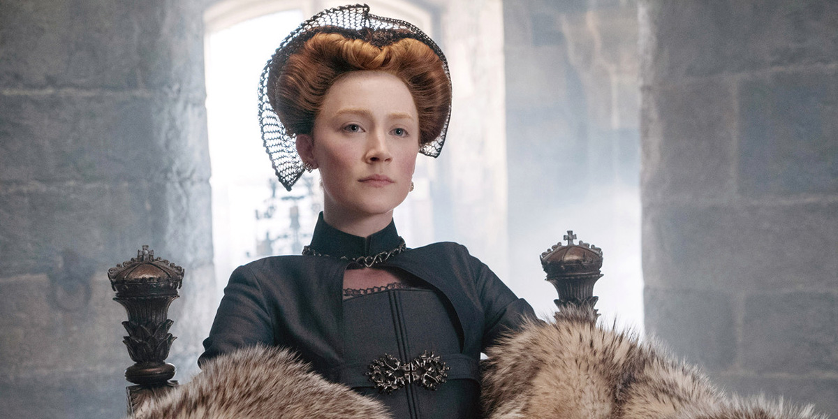Saoirse Ronan as Mary Stuart, wearing a stiff black high neck dress, wrapped in furs, and sitting on a throne