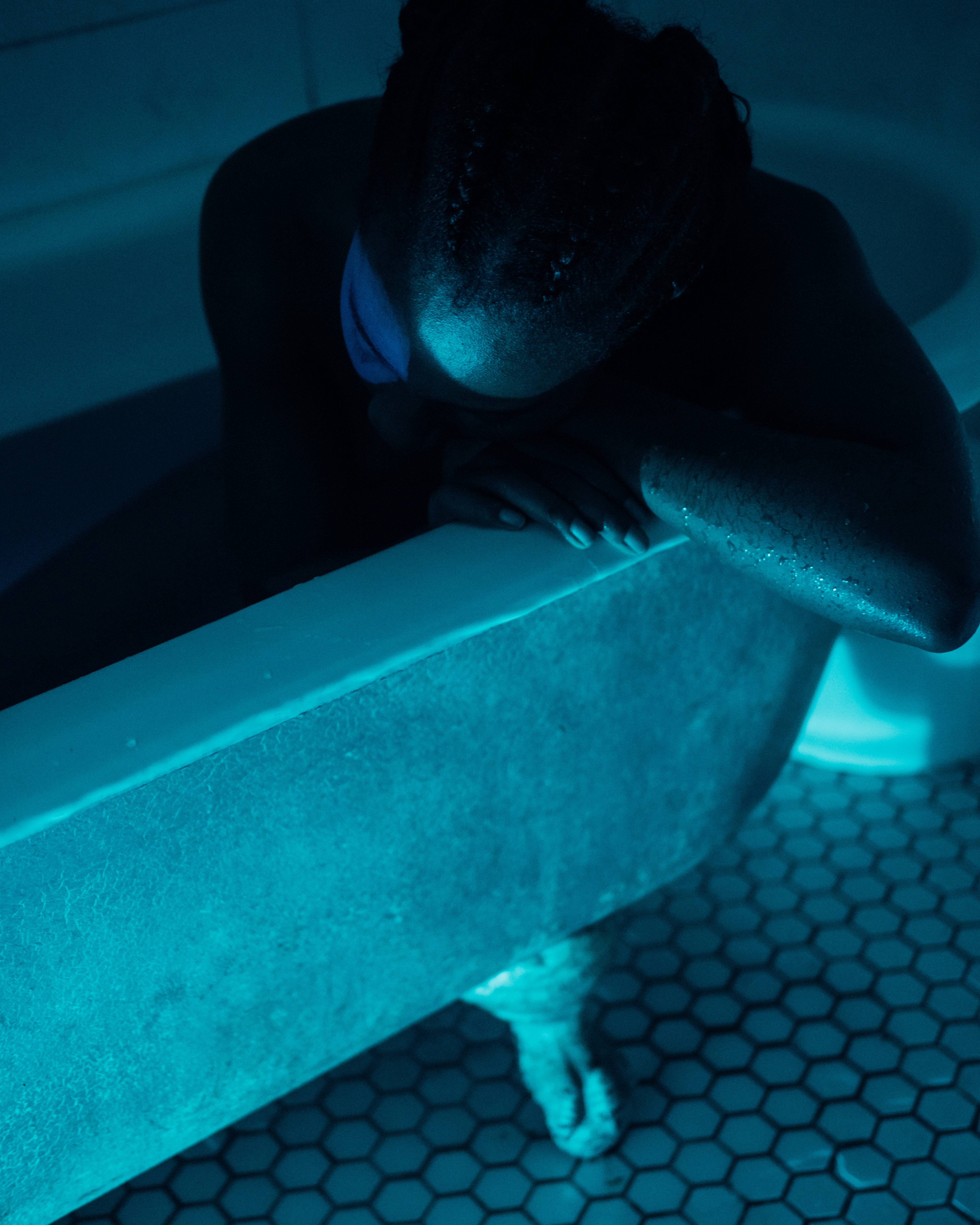 a Black woman with her hair in a cornrowed ponytail sits in a tub with her head in her hands
