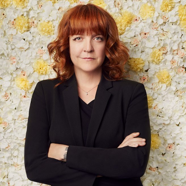 AG, a red-haired woman wearing a black blazer, poses with her arms crossed