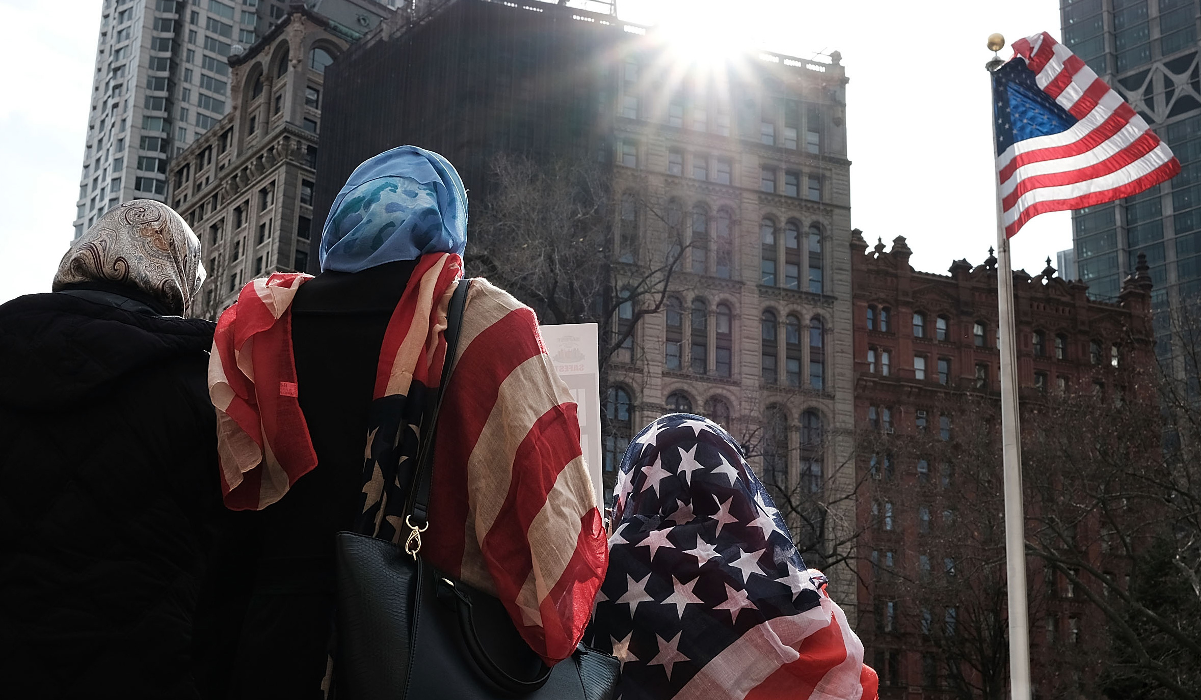 Three women wearing hijabs look up at an American flag. In that same direction, the sun shines over tall buildings in the background.