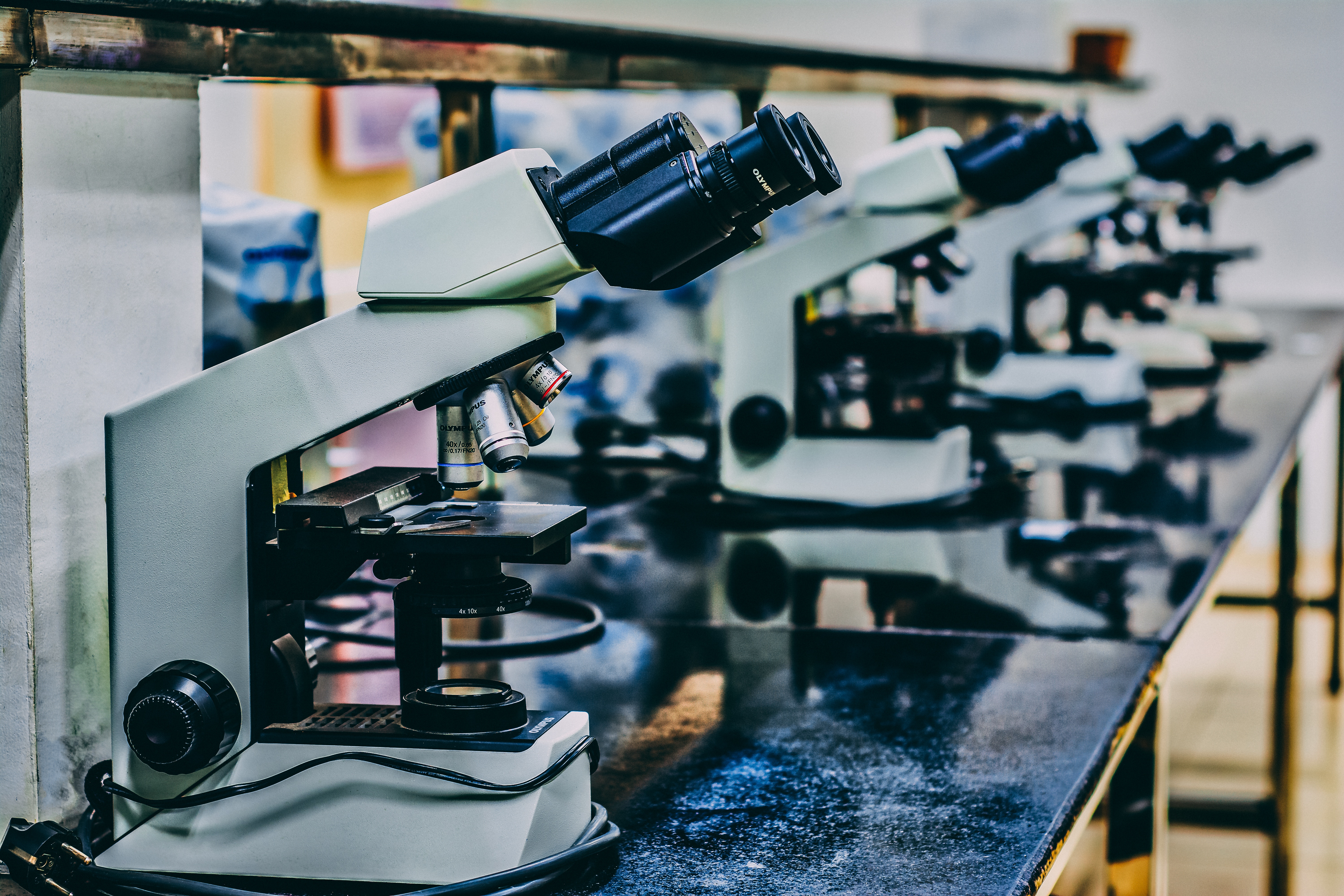 a close-up photo of a row of microscopes in a lab