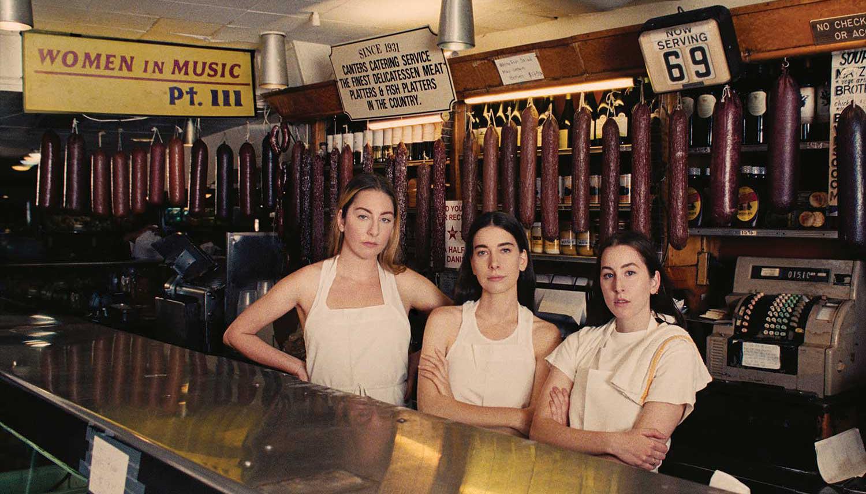 Danielle, Este, and Alana Haim, three white sisters,