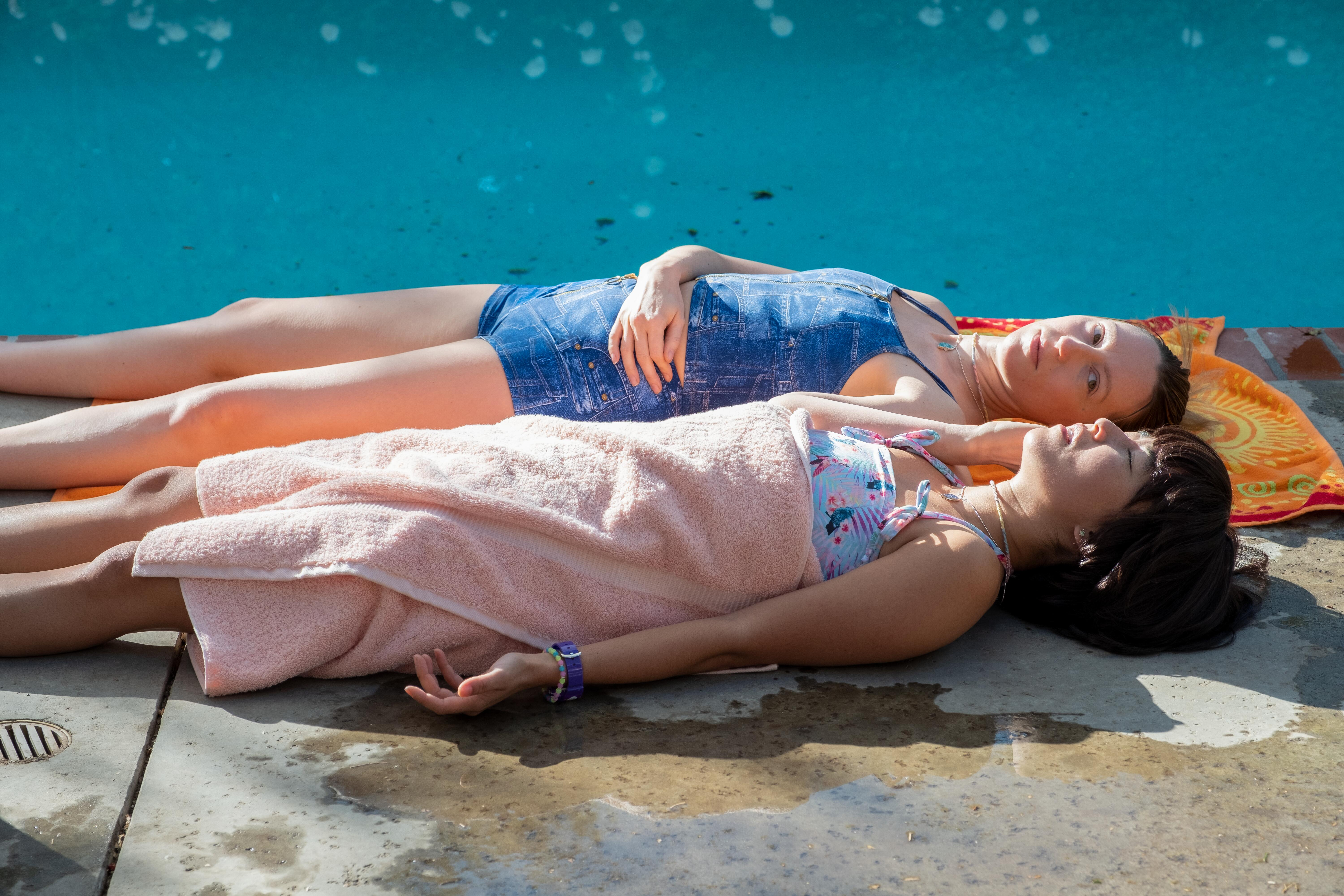 Anna and Maya, two teen girls, lay poolside.