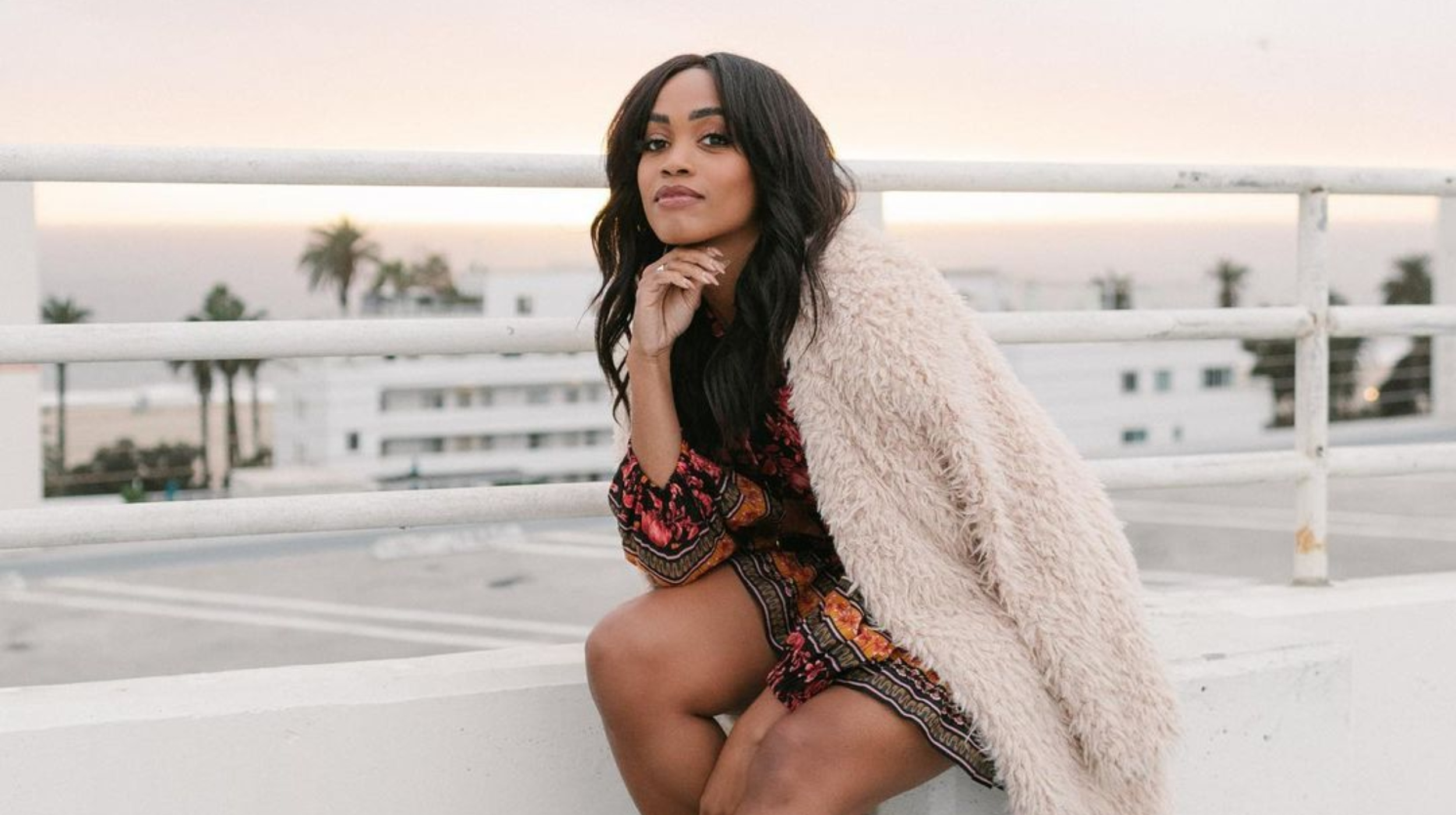 Rachel Lindsay, a Black woman with long, dark hair, smiles. She wears a dress and a white fur coat and sits on a rooftop.