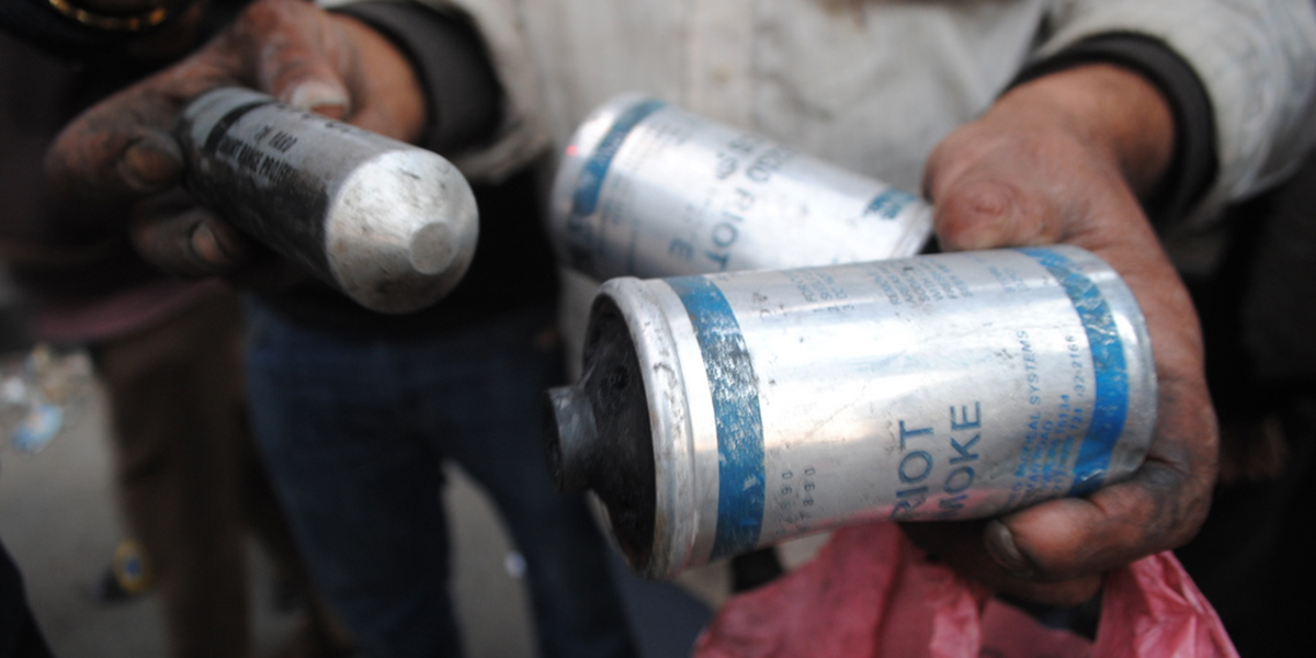 The hands of a person holding three used canisters of tear gas