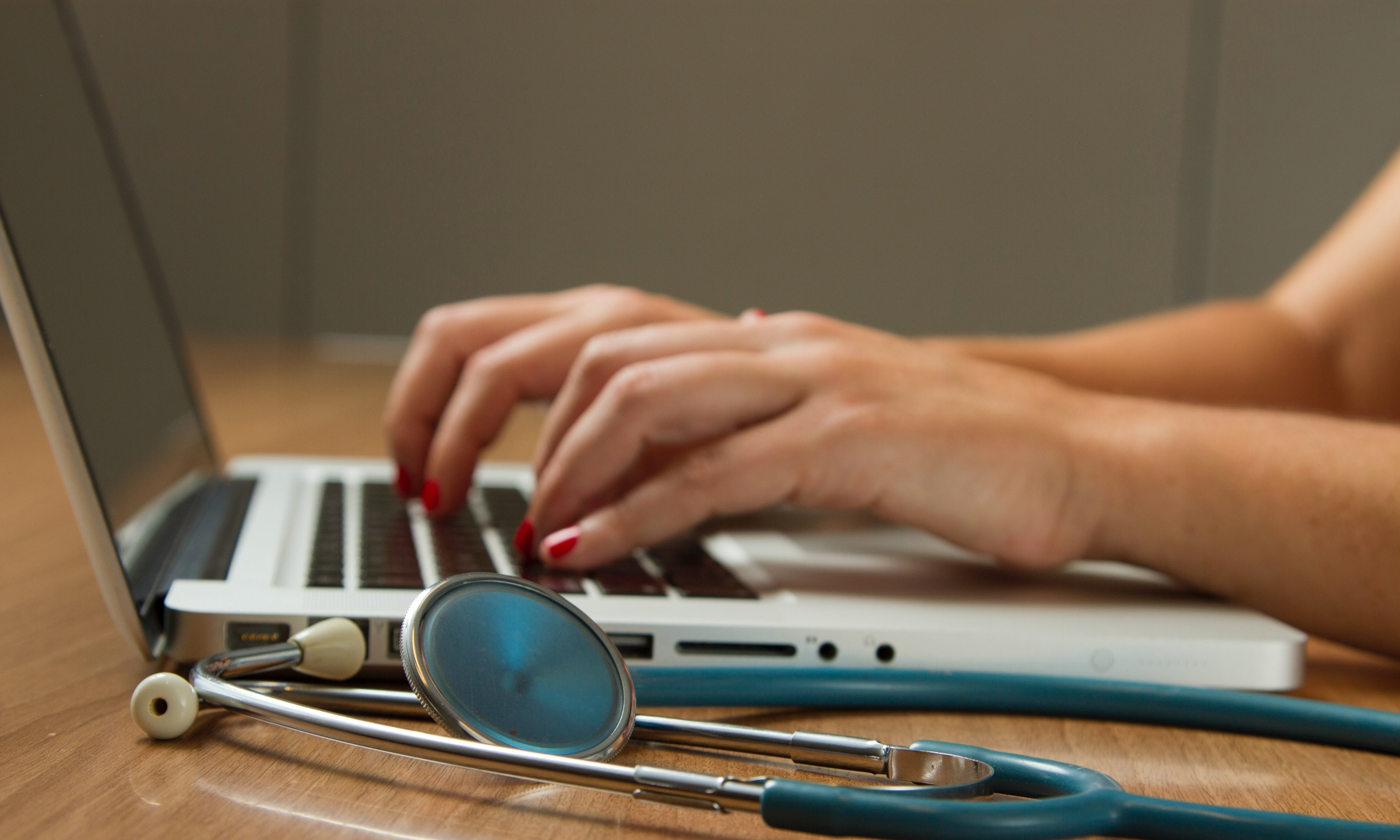 White hands with pink nails typing on a laptop. Next to the laptop is a stethoscope.