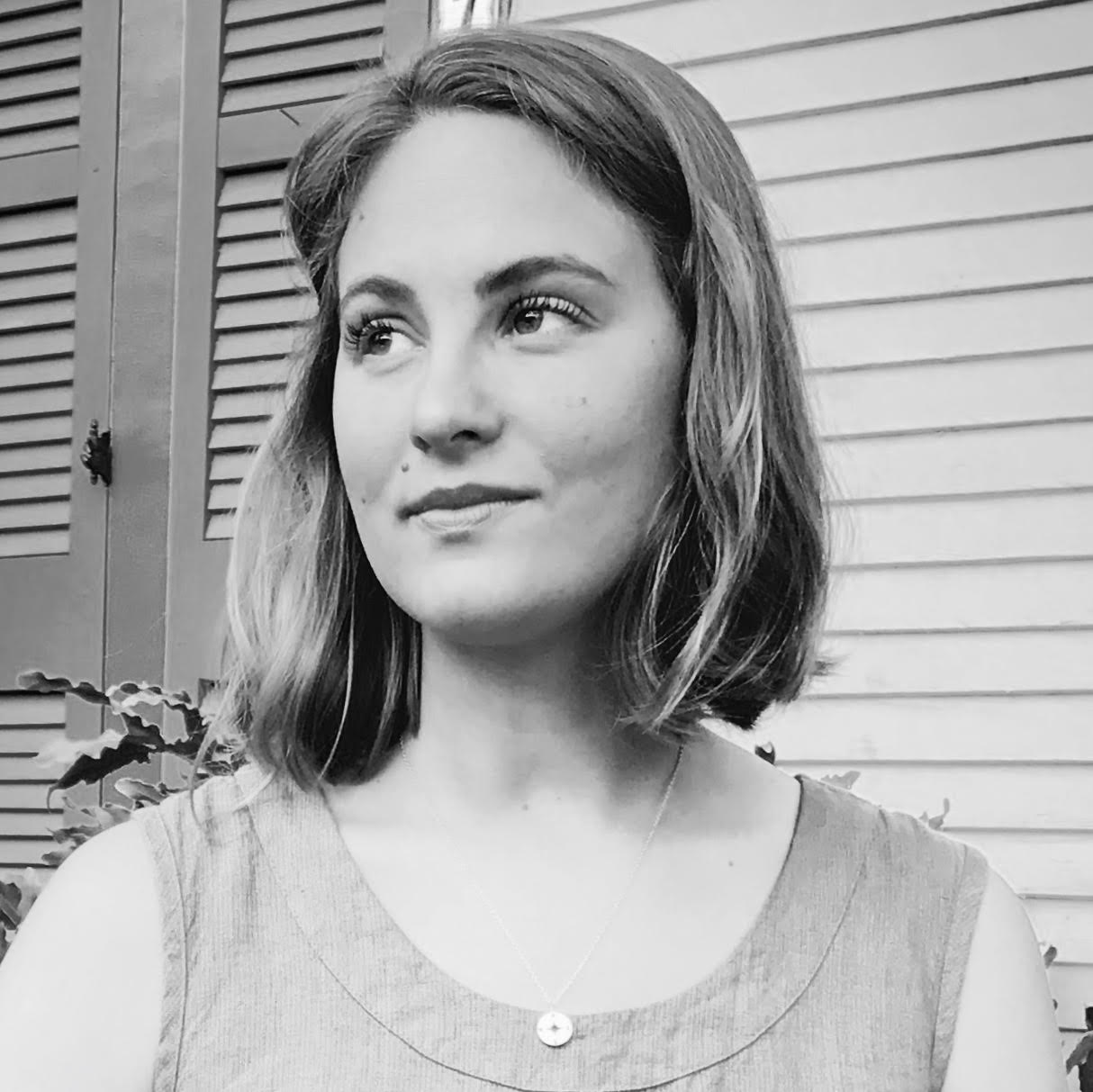 A black and white photo of Lindsay Sproul, a white woman with short blond hair. She looks off into the distance and wears a linen tank top with a small necklace.
