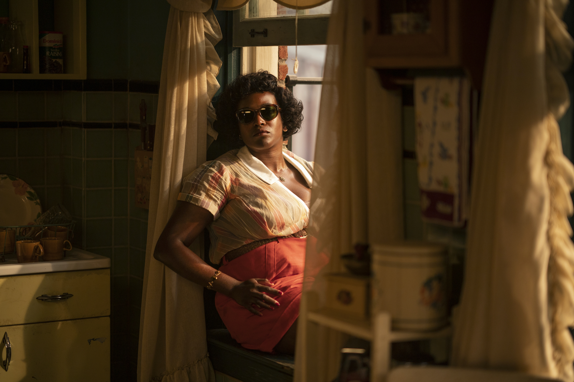 A Black woman sits on a windowsill in a kitchen wearing sunglasses.