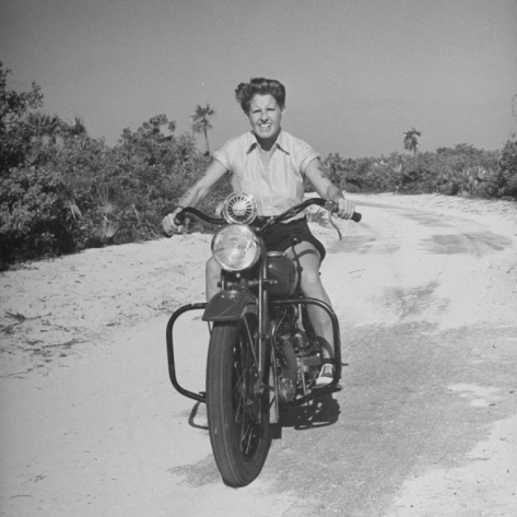 a white woman wearing shirts and a short rides a motorcycle
